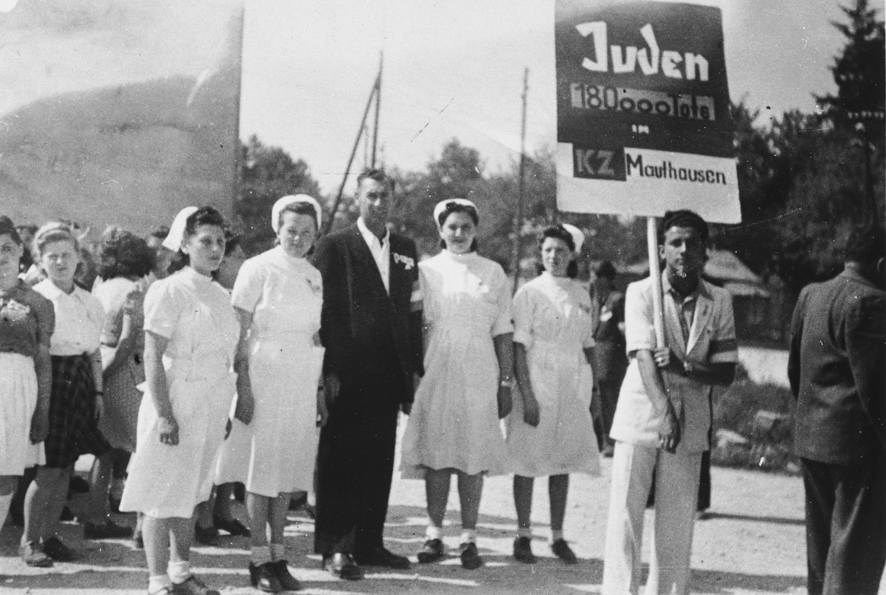 Group portrait of Jewish DPs at a commemoration for the 180,000 Jewish victims of the Mauthausen concentration camp.  Among those pictured are Dr. Reinert and four nurses.