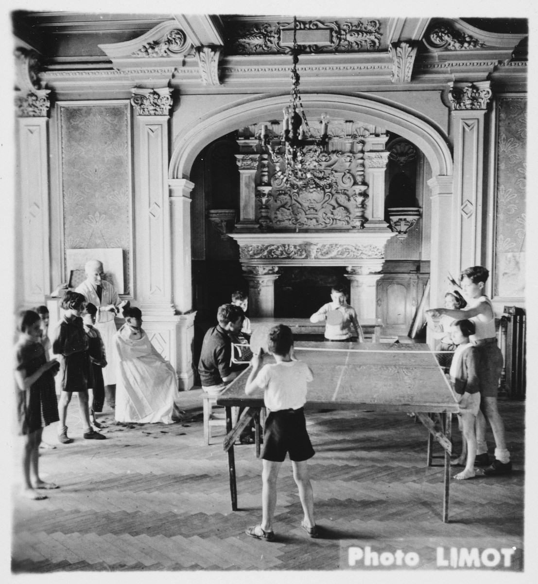 Children play ping pong in a large hall in the Mehoncourt children's home.