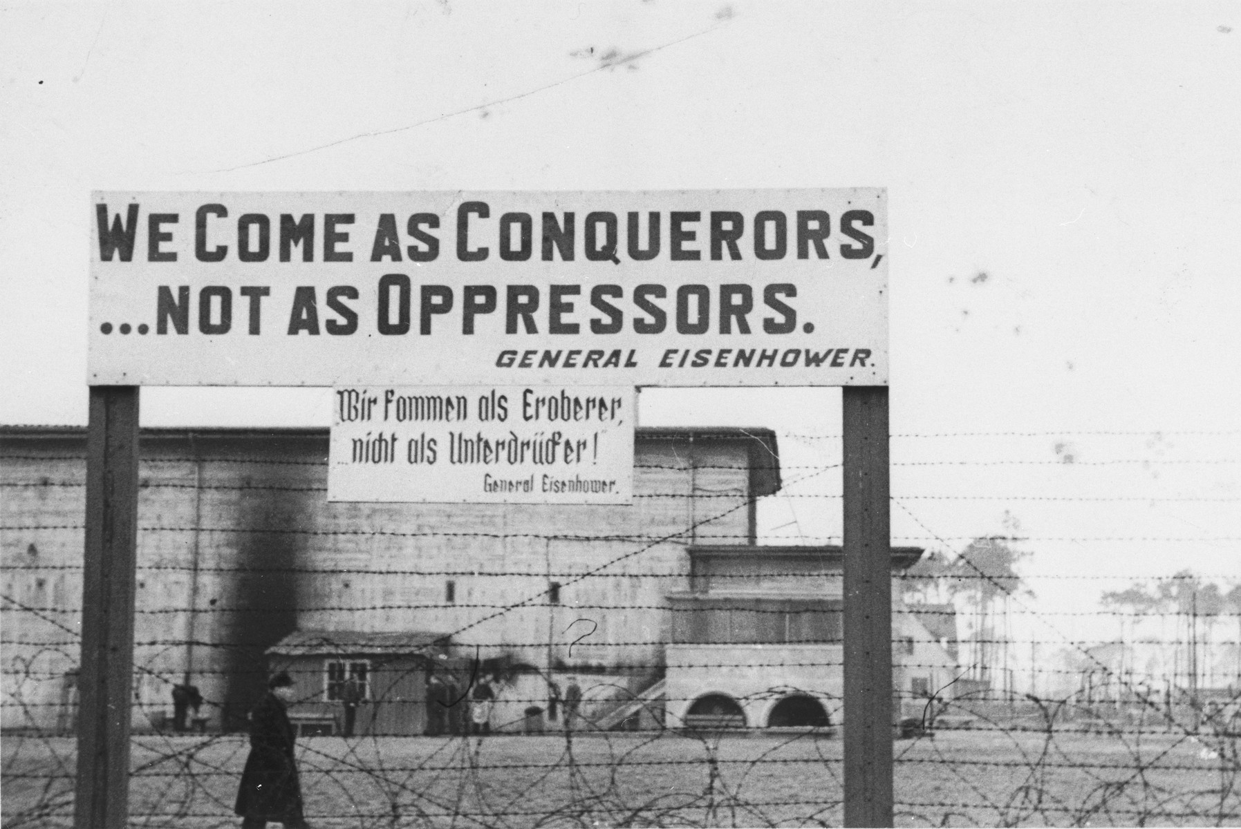 "A sign in front of a U.S. military installation in Berlin features a quotation by General Dwight Eisenhower that reads: ""We Come as Conquerors...Not as Oppressors."""