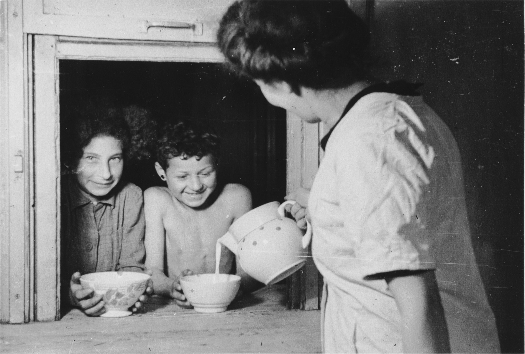 A kitchen worker pours bowls of milk for two children in the Mehoncourt children's home.
