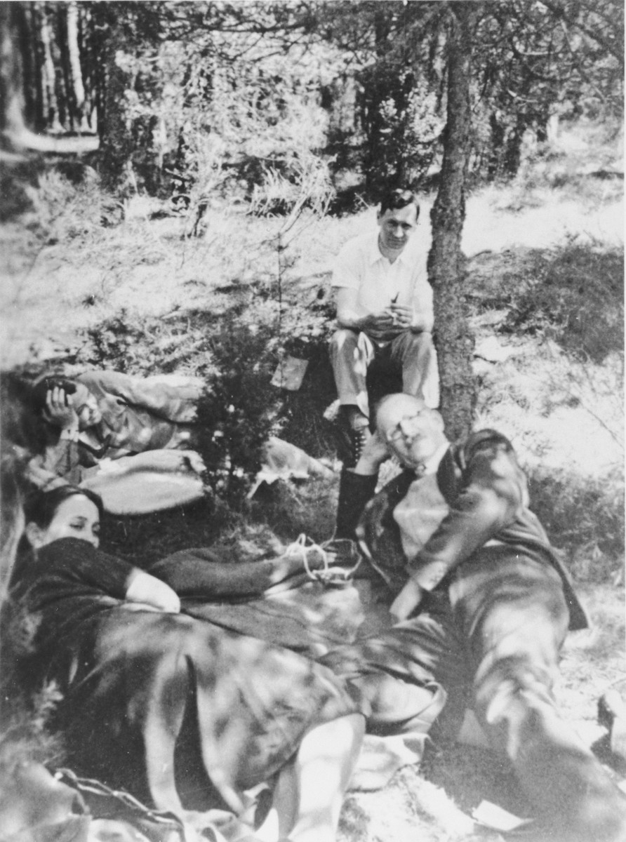 Pastor André Trocmé and assistant pastor Edouard Theis relax with their wives under a tree in the woods.  Pictured clockwise from the top are: Edouard Theis, André Trocmé, Magda Trocmé, and Mildred Theis.