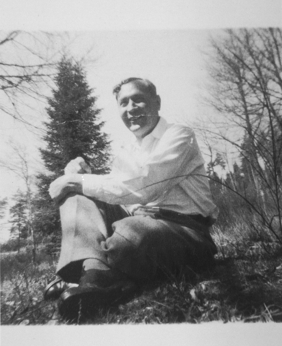 Portrait of pastor Edouard Theis sitting in the grass.