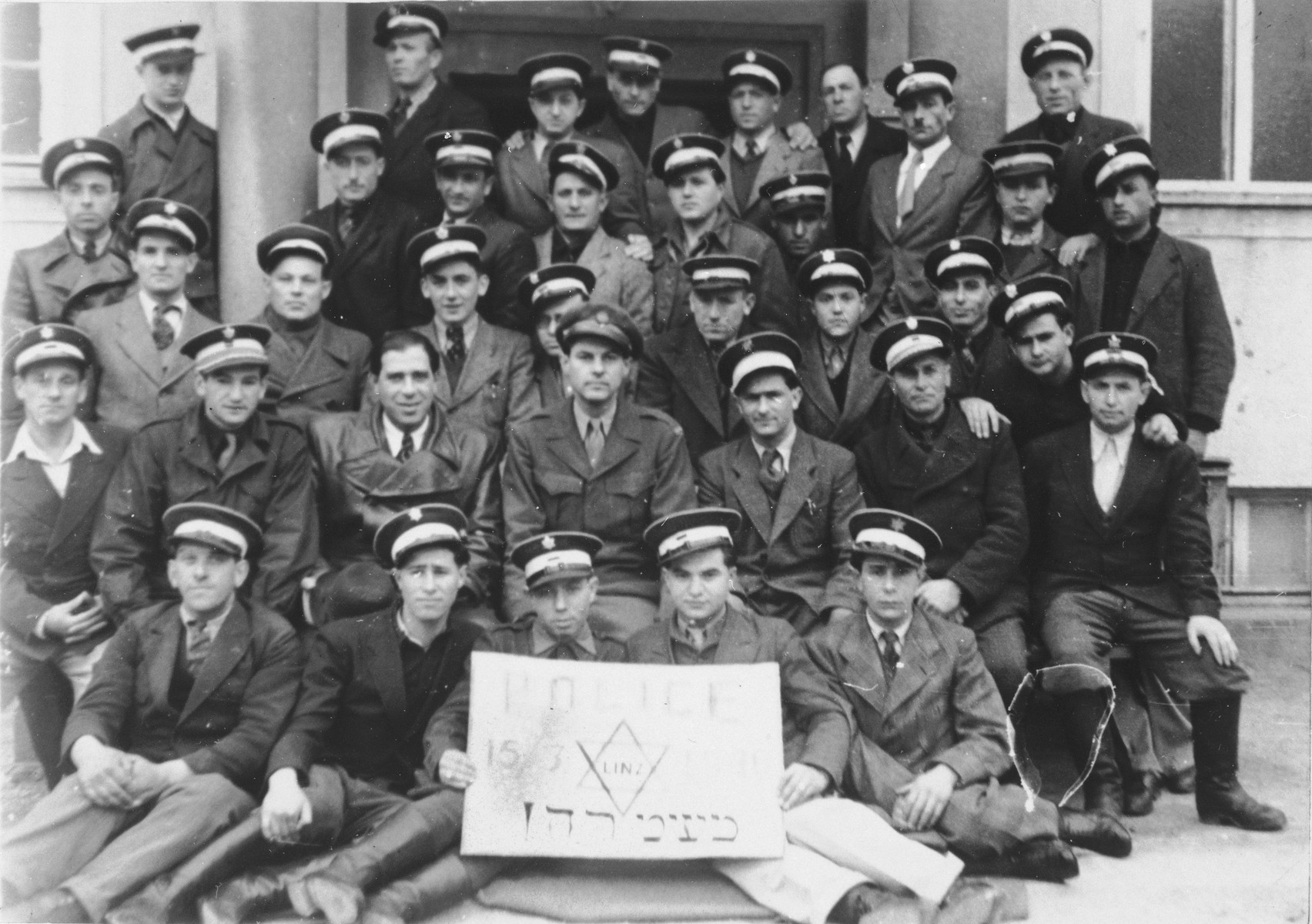 Group portrait of the Jewish police in the Bindermichl displaced persons camp.  Among those pictured is Willie Abraham. is holding the sign on the right. He was born in Velki-Rokovec, Czechoslovakia on May 1st, 1925.  He survived Gusen in Mauthausen. Also pictured is Shimon (Sol) Wizel, seated to the right of Willie. Your message:: The man in the second row from the bottom, Josef Sterngast. (not wearing a hat) is pictured third from the left. He was from Krakow, Poland and on Schindler's List.