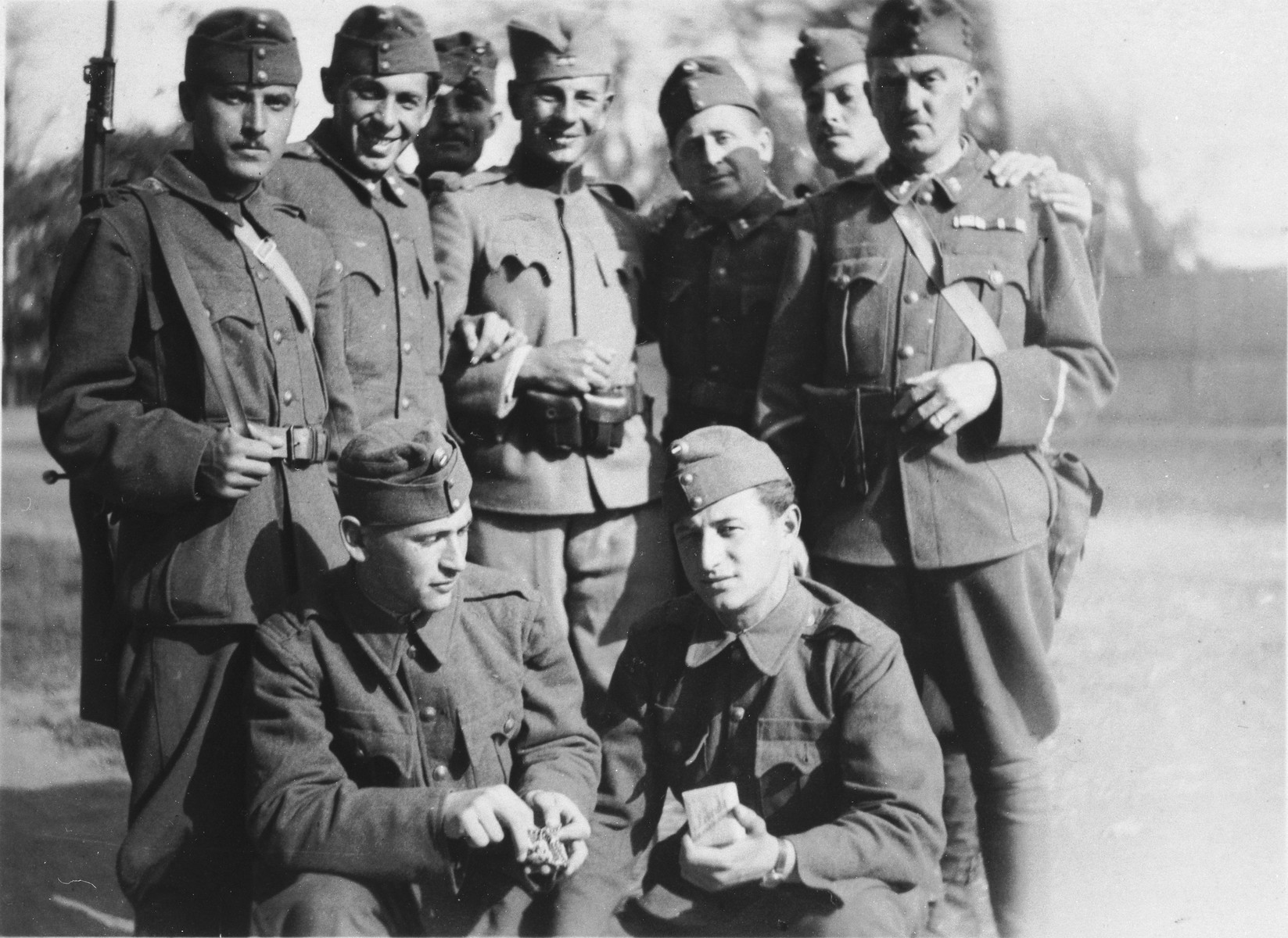 Group portrait of former Jewish soldiers now conscripted into a Hungarian forced labor battalion.  Jeno Lebowiz is pictured in the front, right corner.