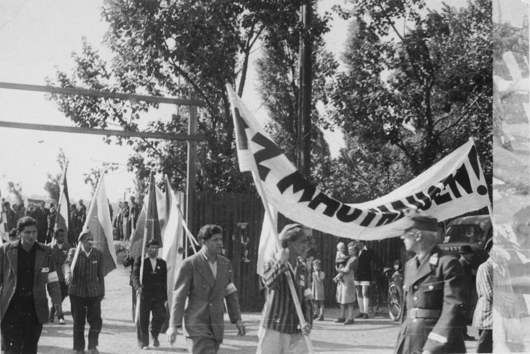 Jewish DPs march with banners and flags in the Bindermichl displaced persons camp to commemorate the Jewish victims of the Mauthausen concentration camp.
