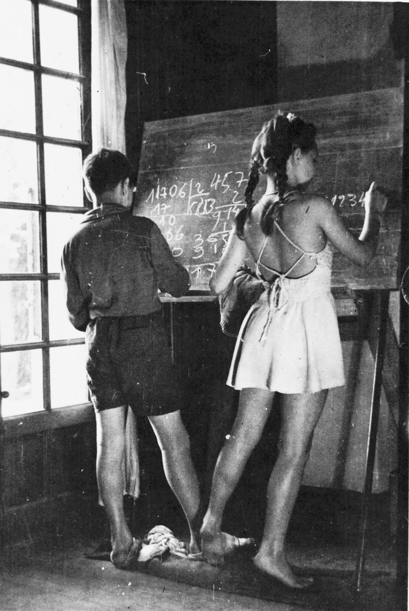 Two children write equations on the blackboard during a mathematics lesson at in the Mehoncourt children's home.