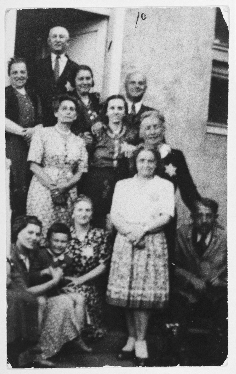 A group of Hungarian Jews, some wearing the yellow star, pose on the steps of a building in Pecs.  Among those pictured is Erzsebet (Singer) Doczi, the donor's mother-in-law.  She was later killed in Auschwitz.
