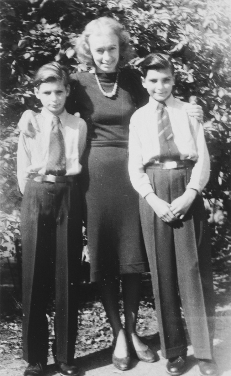 Two Jewish brothers pose with the adopted daughter of their German rescuer.  Pictured from left to right are Henri Taucher, Traute Holinover and Horst Taucher.  Traute Holinover was the only person besides her mother who knew the boys were Jewish.  She worked as an official Nazi party photographer which enabled her to get the boys ration cards and other necessities.
