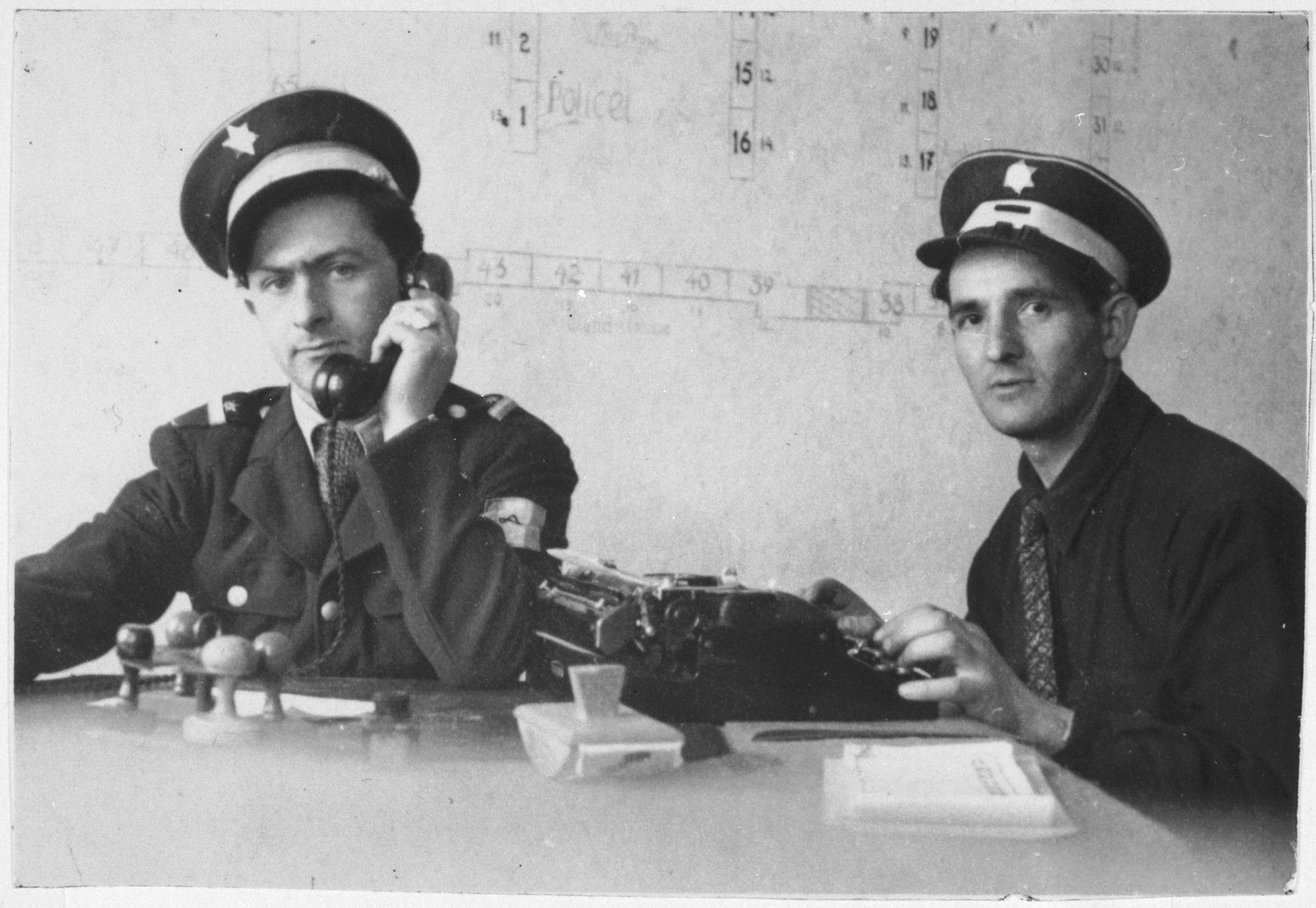 Two Jewish policemen at work in their office at the Bindermichl displaced persons camp.  Pictured on the left is police chief Willie Sterner.
