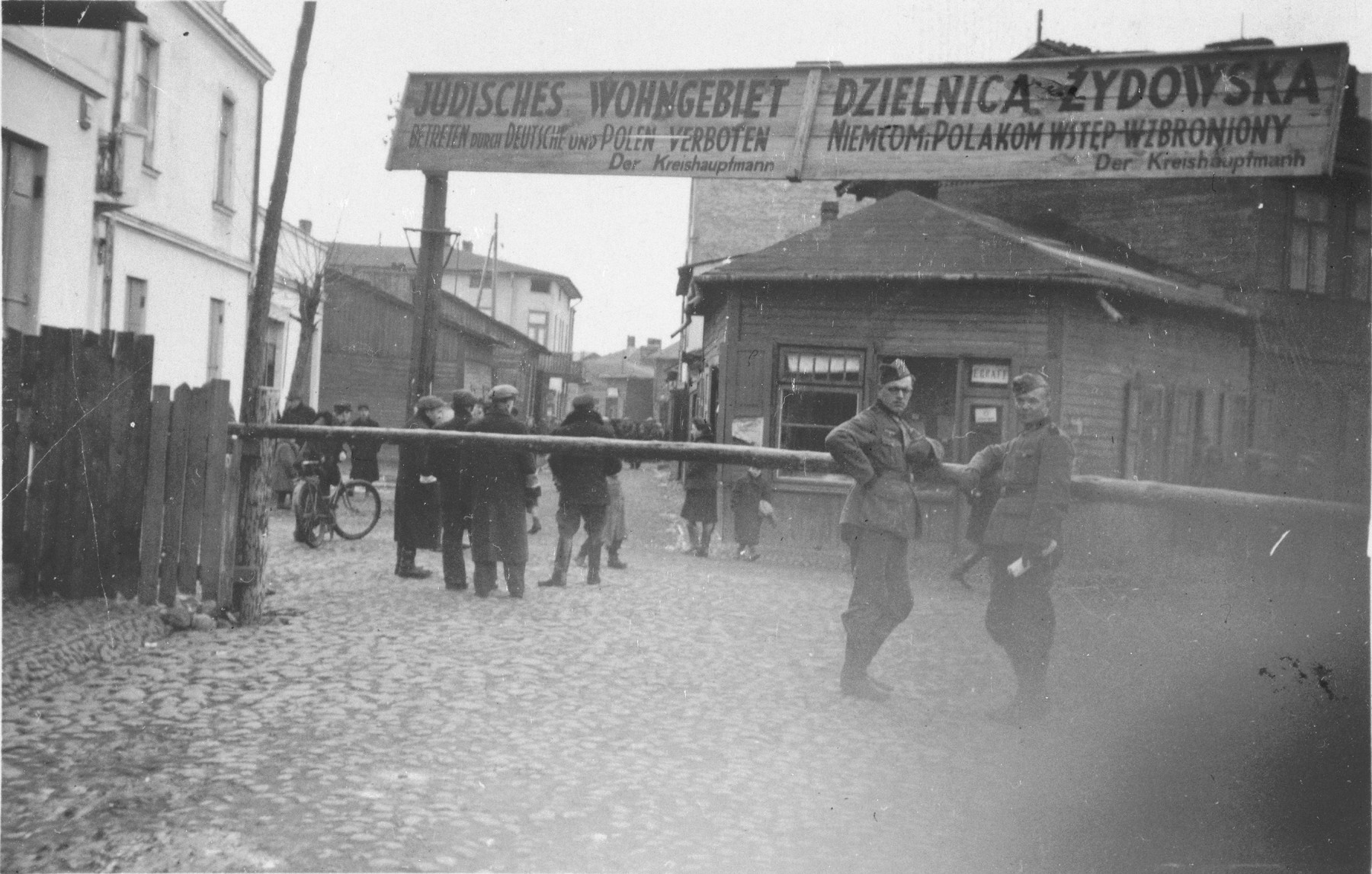 Two German soldiers pose at the entrance to an unidentified ghetto in Poland.    The sign in Polish and German states that entrance to the Jewish quarter is forbidden to Germans and Poles.