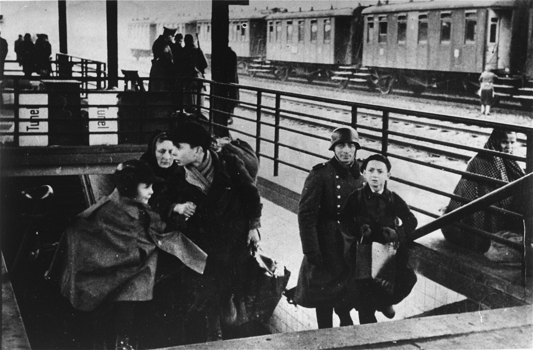 A Jewish family climbs the stairs to the train platform at the railway station during a deportation action from the Krakow ghetto.
