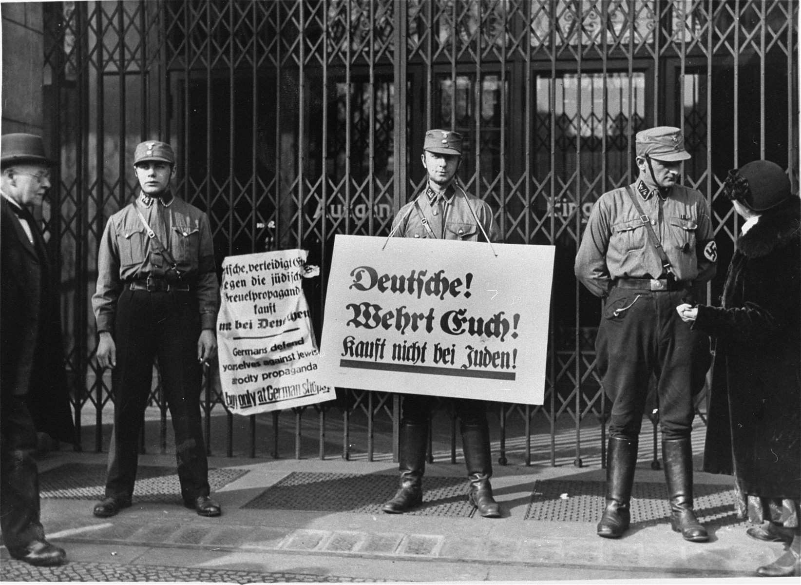 "SA pickets, wearing boycott signs, block the entrance to a Jewish-owned shop.    The signs read:  ""Germans, defend yourselves against the Jewish atrocity propaganda, buy only at German shops!"" and ""Germans, defend yourselves, buy only at German shops!"""
