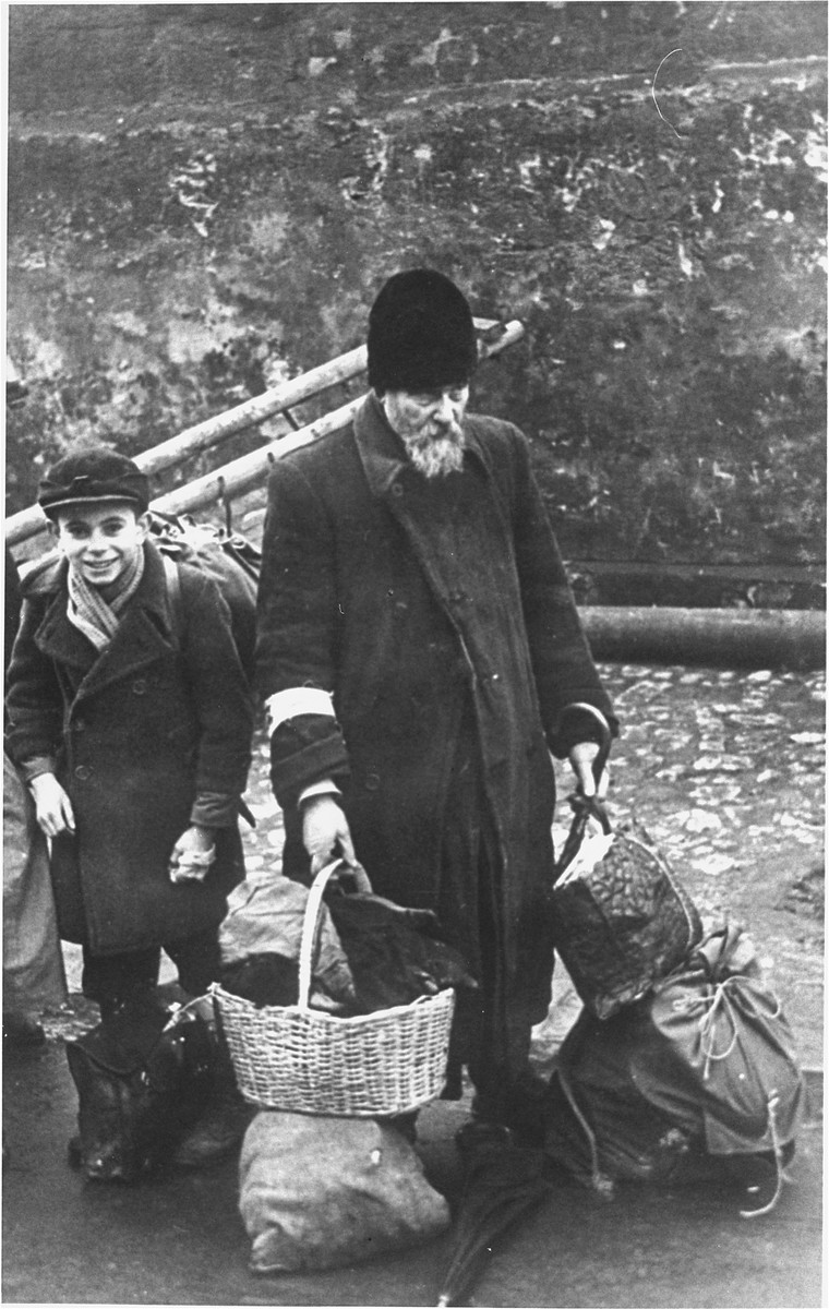 An elderly man and child who have been rounded-up for deportation wait with their luggage at an assembly point in the Krakow ghetto.   [detail of w/s 02144]