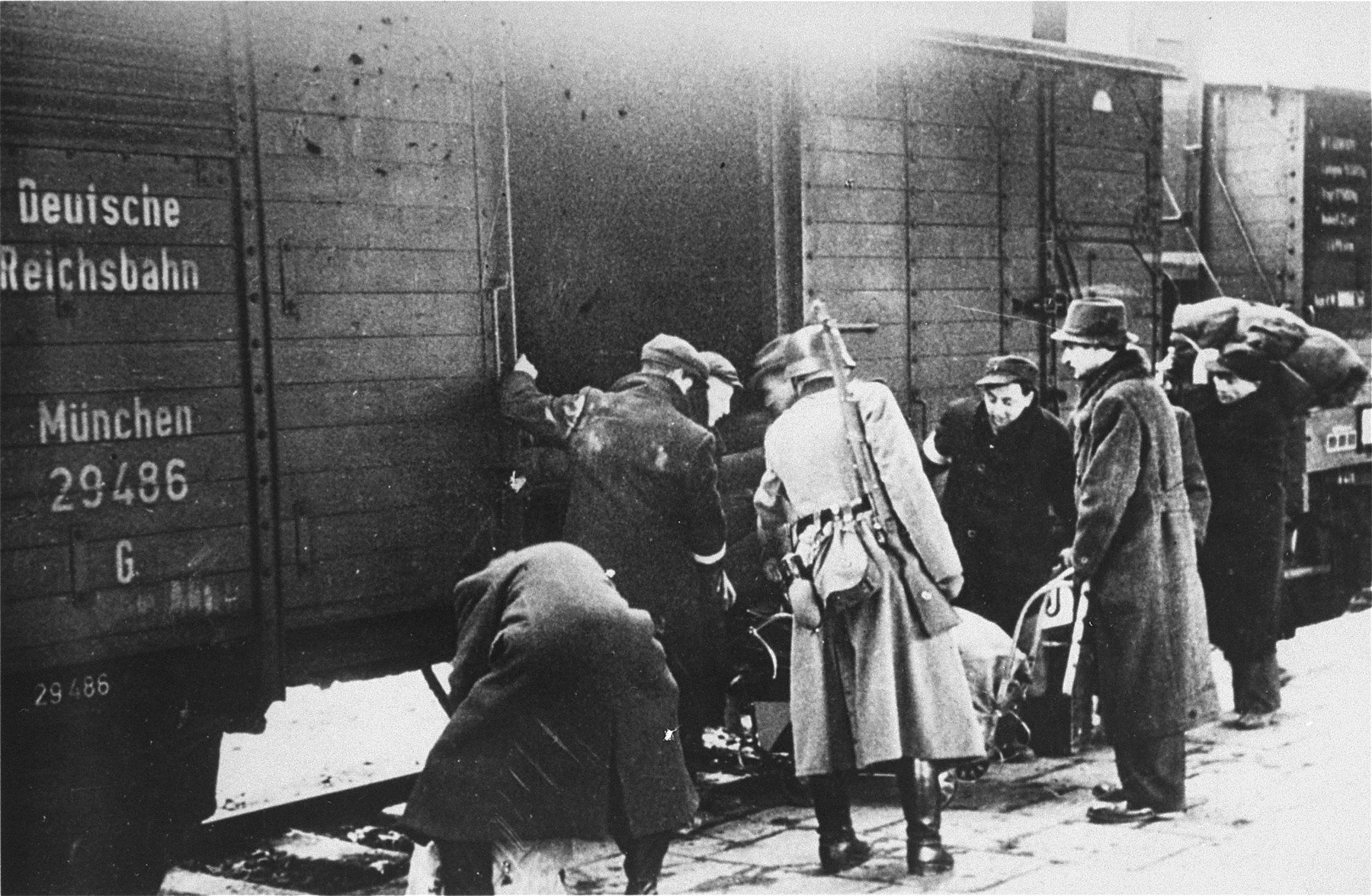 A member of the German SS supervises the boarding of Jews onto trains during a deportation action in the Krakow ghetto.