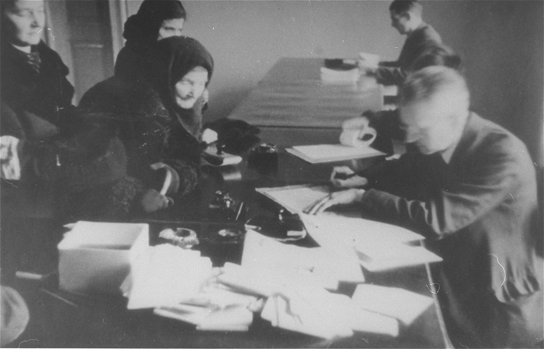Jews obtaining work permits or ID cards in an administrative office in the Krakow ghetto.