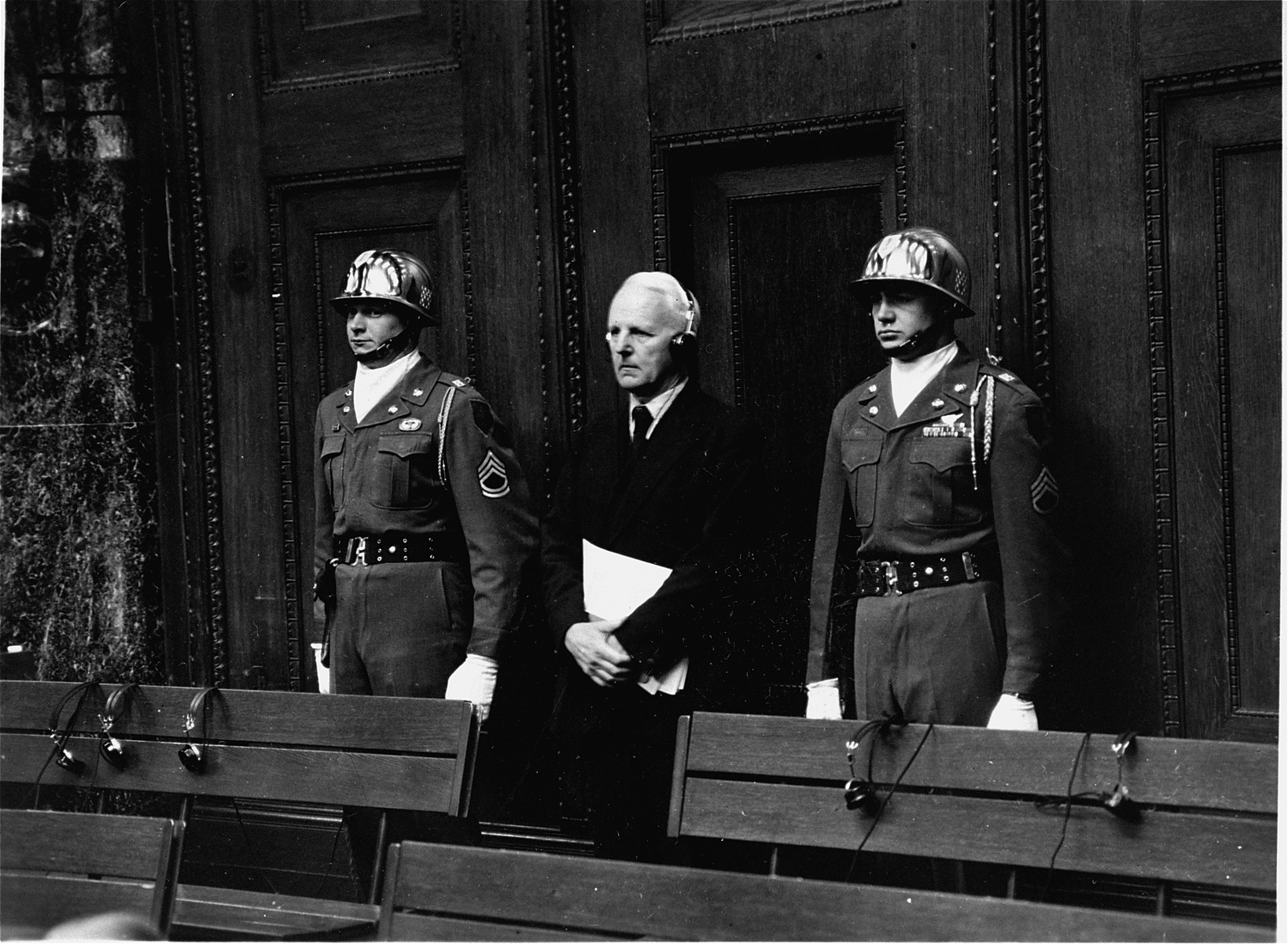 Defendant Ernst Von Weizsaecker, flanked by two guards from the U. S. First Infantry Divisions's 16th Infantry Regiment, listens his sentence of 7 years imprisonment following the conclusion of the Ministries Trial.