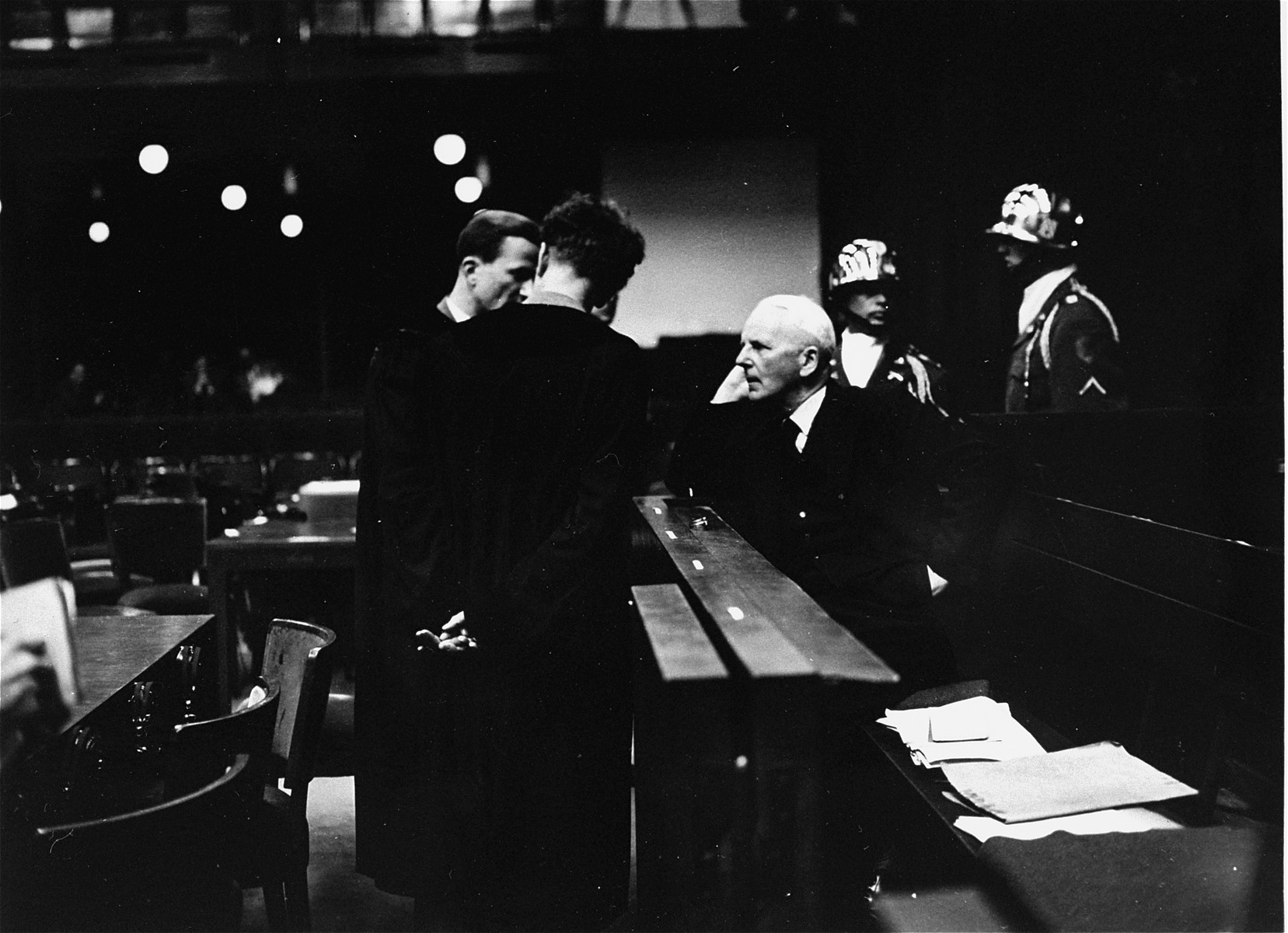 Ernst von Weizsaecker, former State Secretary in the German Foreign Office and last German Ambassador to the Vatican, speaks with his son Richard, acting as his co-defense counsel, and Dr. Harmut Becker, Weiszacker's main counsel, during the Ministries Trial.