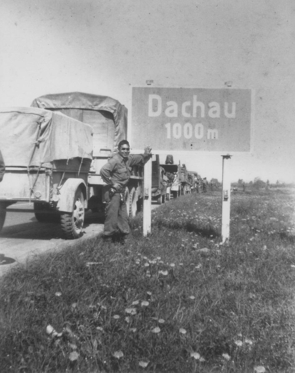 Melvin Hamamoto, a Japanese-American liberator, poses next to a road sign outside of Dachau as trucks with the 522nd Field Artillery Battalion press on towards the town.