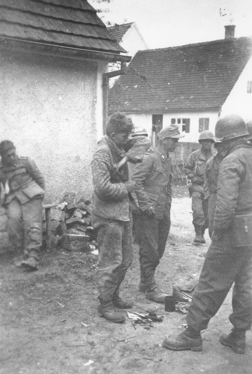Japanese-American troops with the 522nd Field Artillery Battalion collect the belongings of three captured German Waffen-SS soldiers.