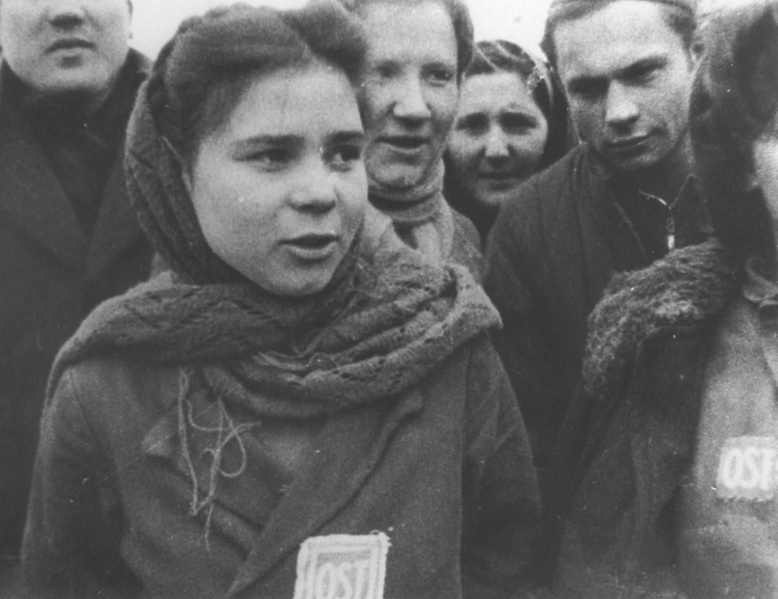 """Female forced laborers wearing """"OST"""" [Ostarbeiter] badges are liberated from a camp near Lodz."""