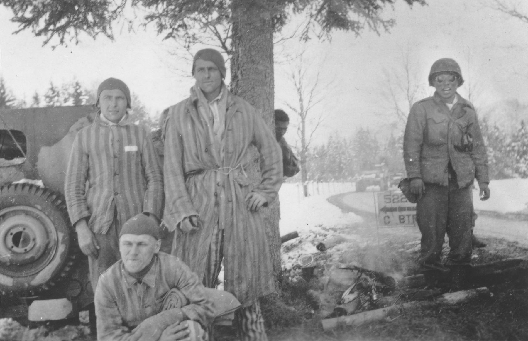 George Oiye (right), a Japanese-American soldier with the 522nd Field Artillery battalion, prepares a camp fire for concentration camp prisoners liberated by his unit near the town of Waakirchen.