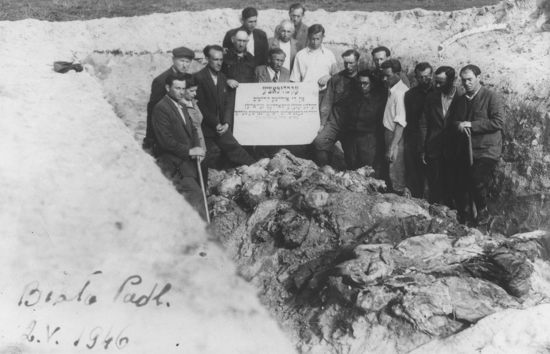 "Jewish survivors stand in an opened mass grave among the exhumed bodies of the victims of a mass shooting in Biala Podlaska.  The Yiddish signs reads, ""Exhumation/ of the Jewish martyrs/ who were murdered/ by the beastial Hitlerite murderers/ Biala Podlaska April 25, 1946."""