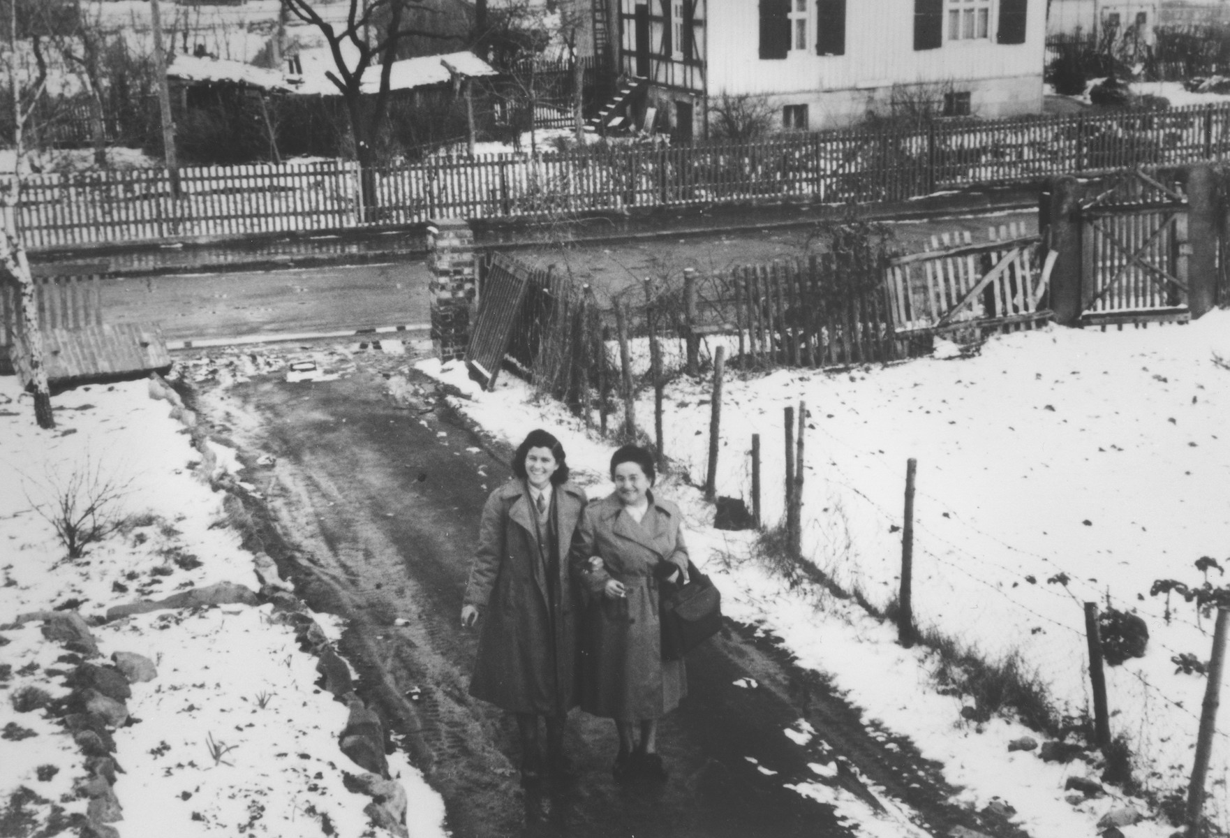 Two Jewish female relief workers walk along a path in the Herzog displaced persons camp.  Pictured on the left is Miriam, a sabra sent by the Jewish Agency for Palestine to teach Hebrew to Jewish DPs.  On the right is Mrs. Greenberg from the American Jewish Joint Distribution Committee in New York.