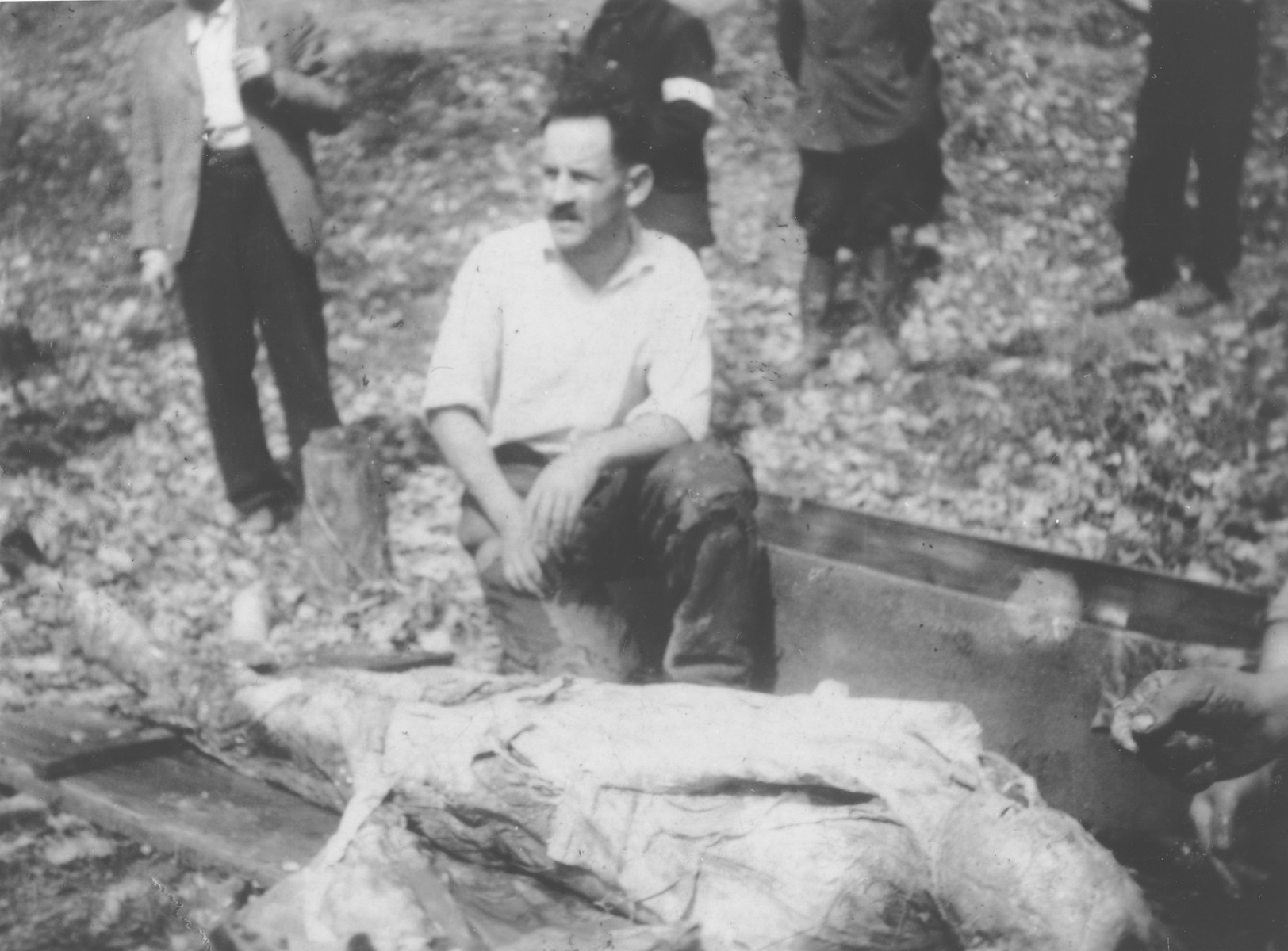 Jozsef Gecse, a Hungarian Nazi who was active in the ghetto, sits next to the body of a Jew killed in the ghetto in Dej