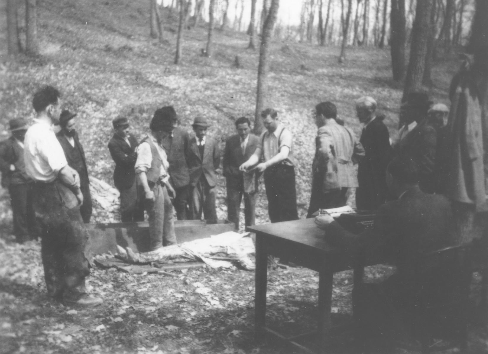 Romanian workmen examine the body of a Jew killed in the ghetto in Dej.