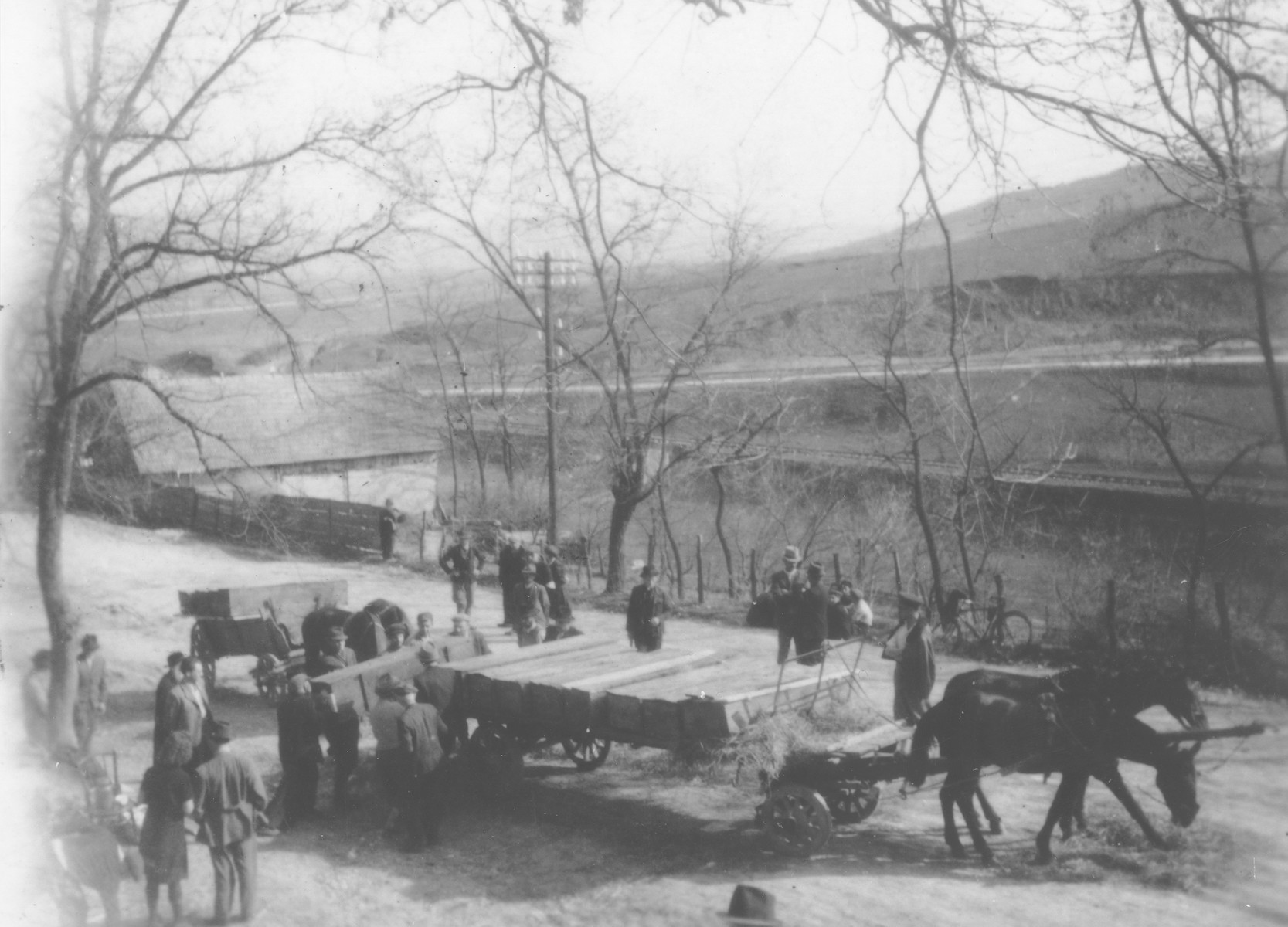 Romanian workmen load coffins onto a cart to be transported to the Jewish cemetery in Dej.