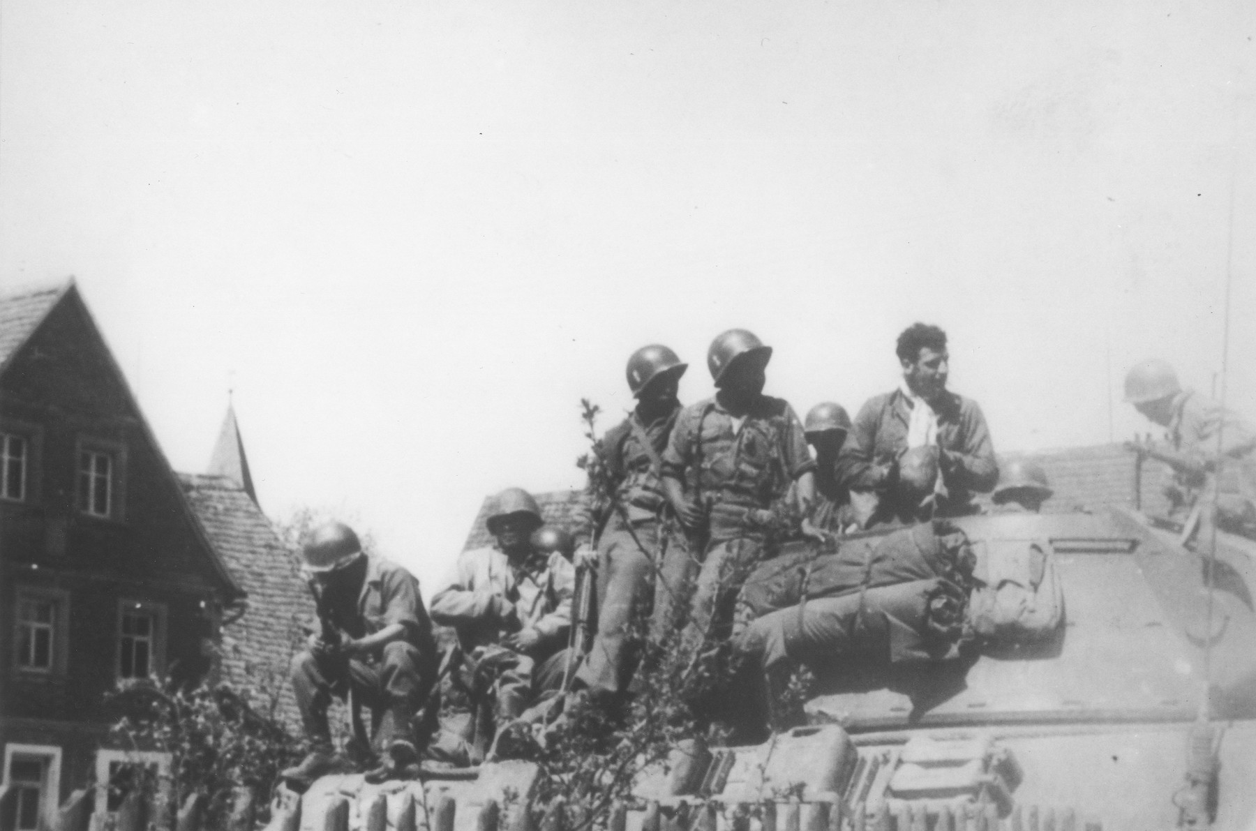 Japanese-American soldiers with the 522nd Field Artillery Battalion catch a ride on a tank destroyer near Dachau.