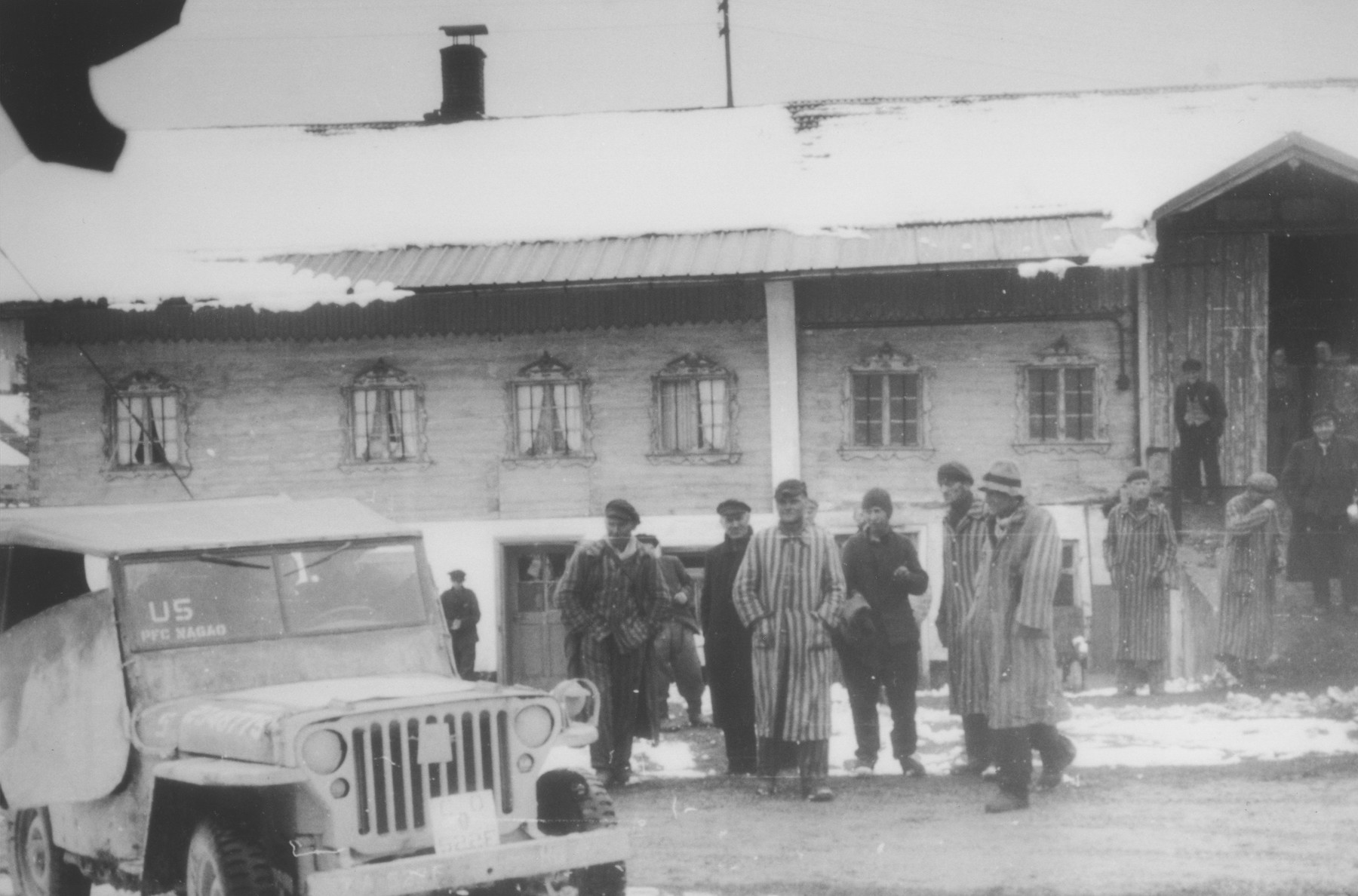 Liberated prisoners from a Dachau death march stand outside of a barn in Waakirchen, Germany, where Japanese-American soldiers with the 522nd Field Artillery Battalion found them shelter.