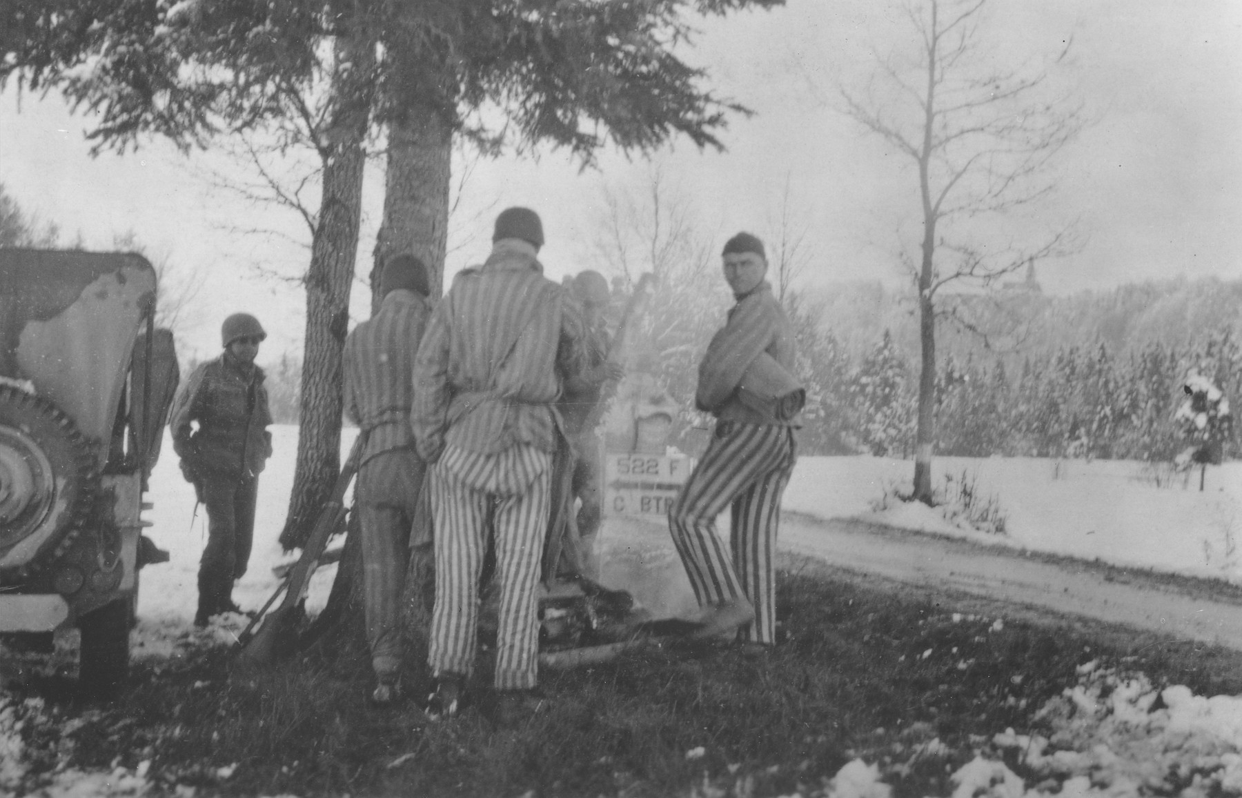 Survivors from a death march from Dachau huddle around a camp fire prepared by Japanese-American soldiers with the 522nd Field Artillery Battalion.    The soldier on the left is George Oiye.