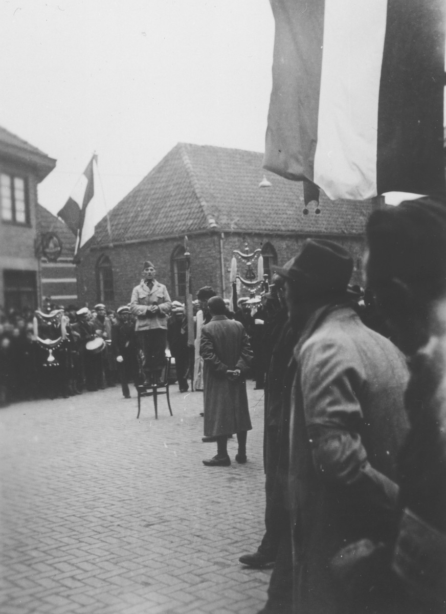 Standing on a chair in the middle of Hagen Street in Eibergen, a local resident delivers a speech at a public celebration of the liberation of eastern Holland.  Directly behind the speaker is the Eibergen synagogue, which ceased to be used by the Jewish community after the war.