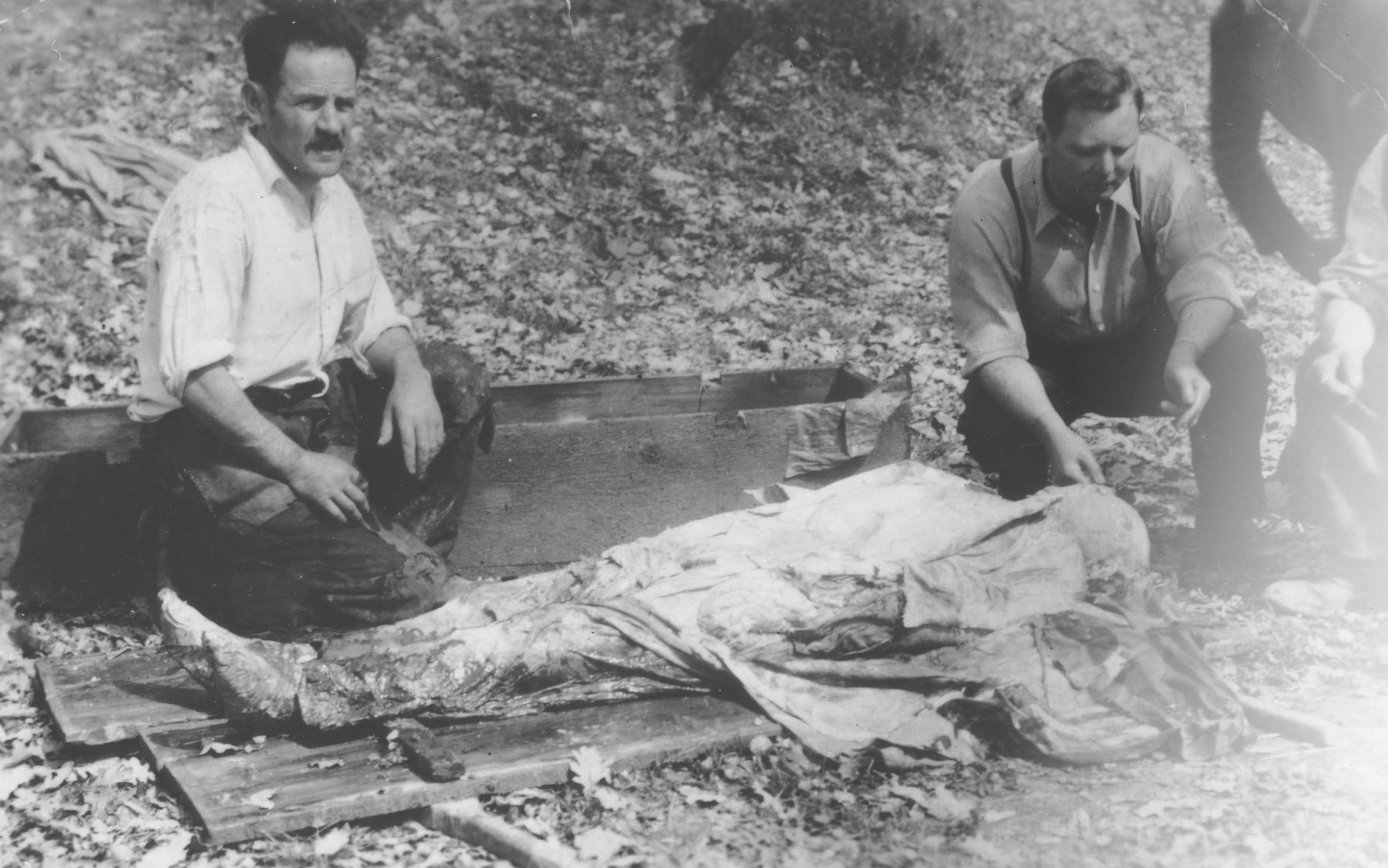 Jozsef Gecse, a Hungarian Nazi who was active in the ghetto, aids a Romanian man examine the body of a Jew killed in the ghetto in Dej.