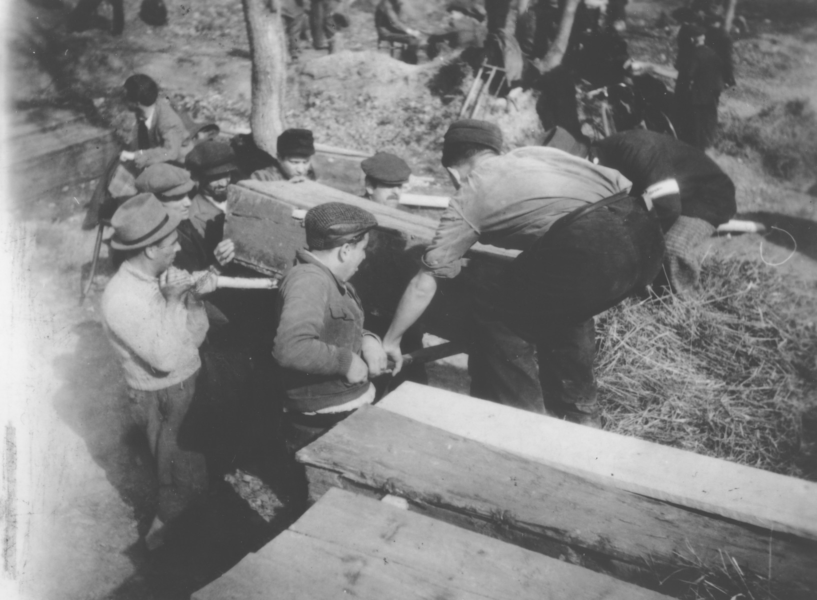 Romanian workmen exhume a coffin containing the body of a Jew killed in the ghetto in Dej.