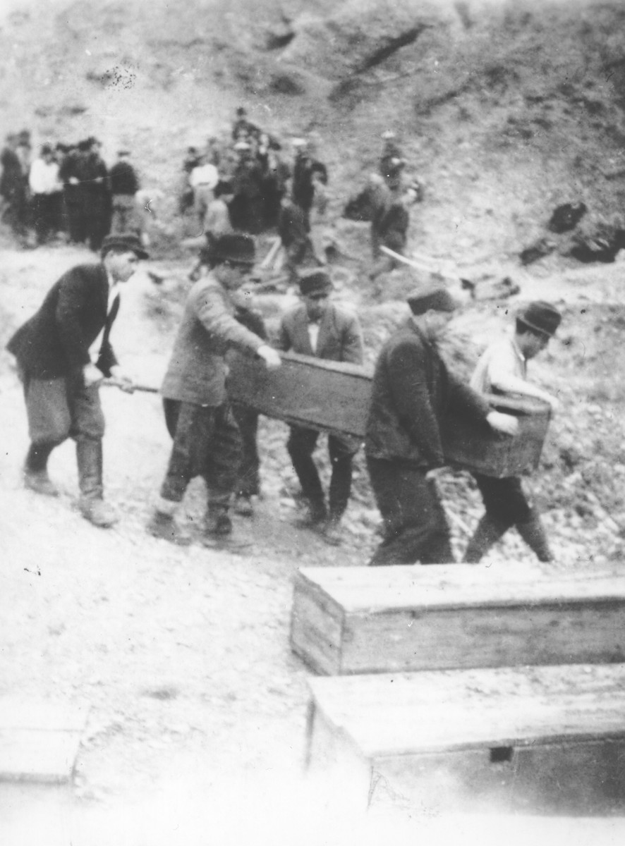 Romanian workmen carry a coffin containing the body of a Jew killed in the ghetto in Dej.
