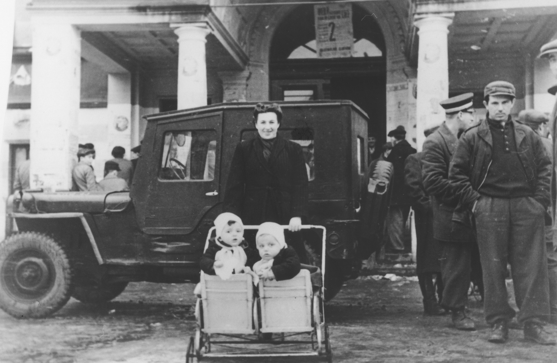 A Jewish mother poses with her twin toddlers outside a building in the Gold Cup displaced persons camp.  These children were the first set of twins born in the camp.