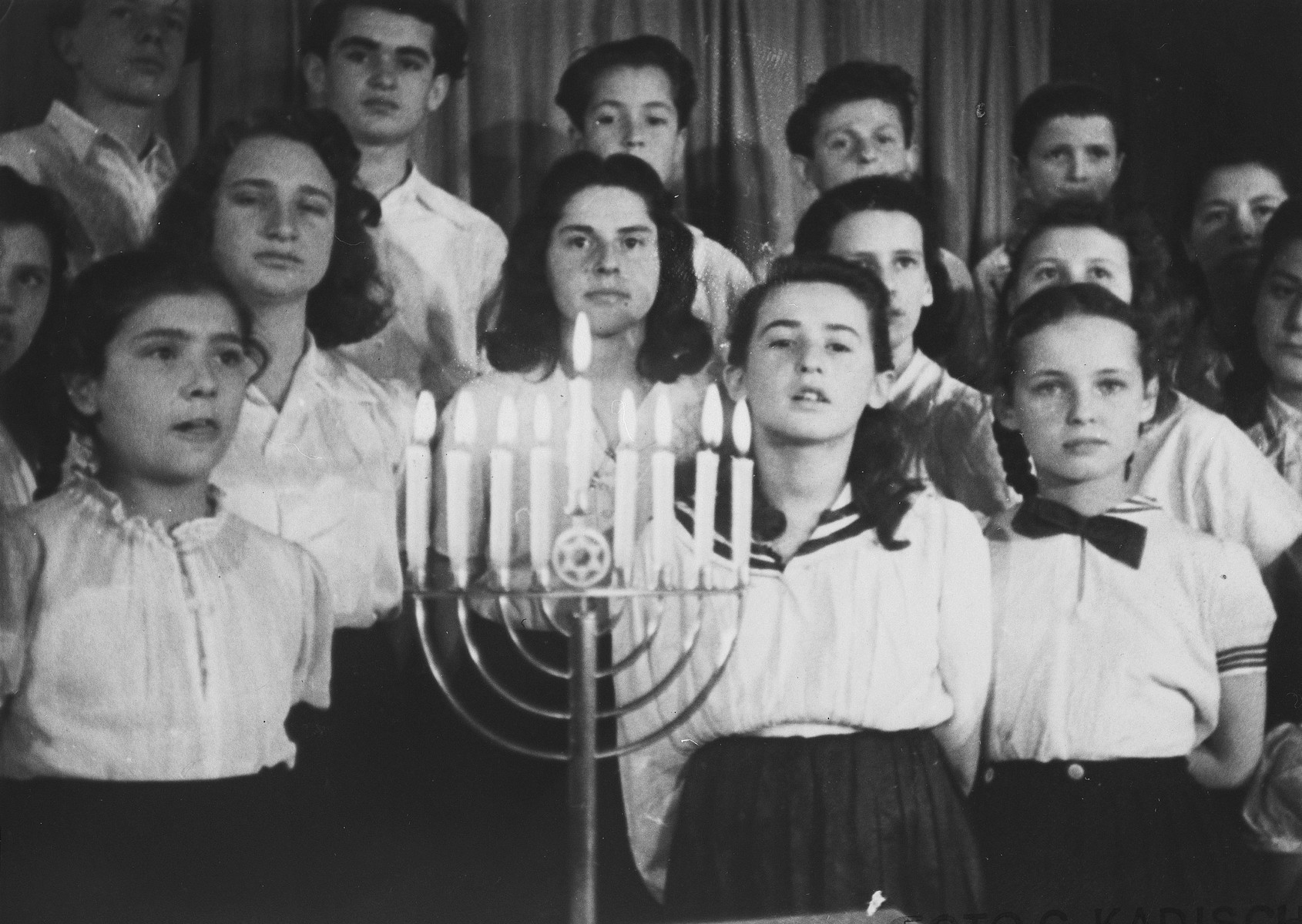 Members of the Dror Zionist youth choir perform at a Hanukkah celebration in the Landsberg displaced persons camp.  Rivka Baran is pictured in the second row from the front, at the left.