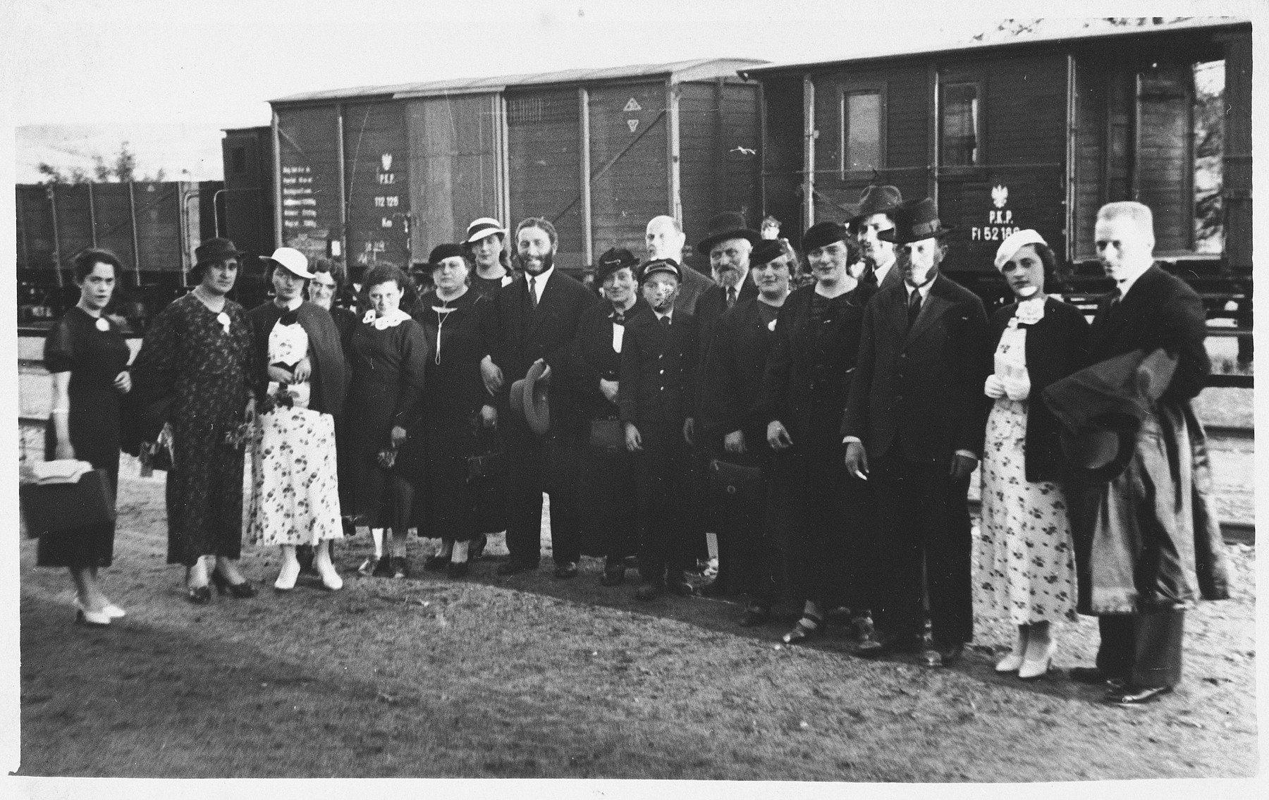 Group portrait of relatives and friends of the Jam family in front of a train.