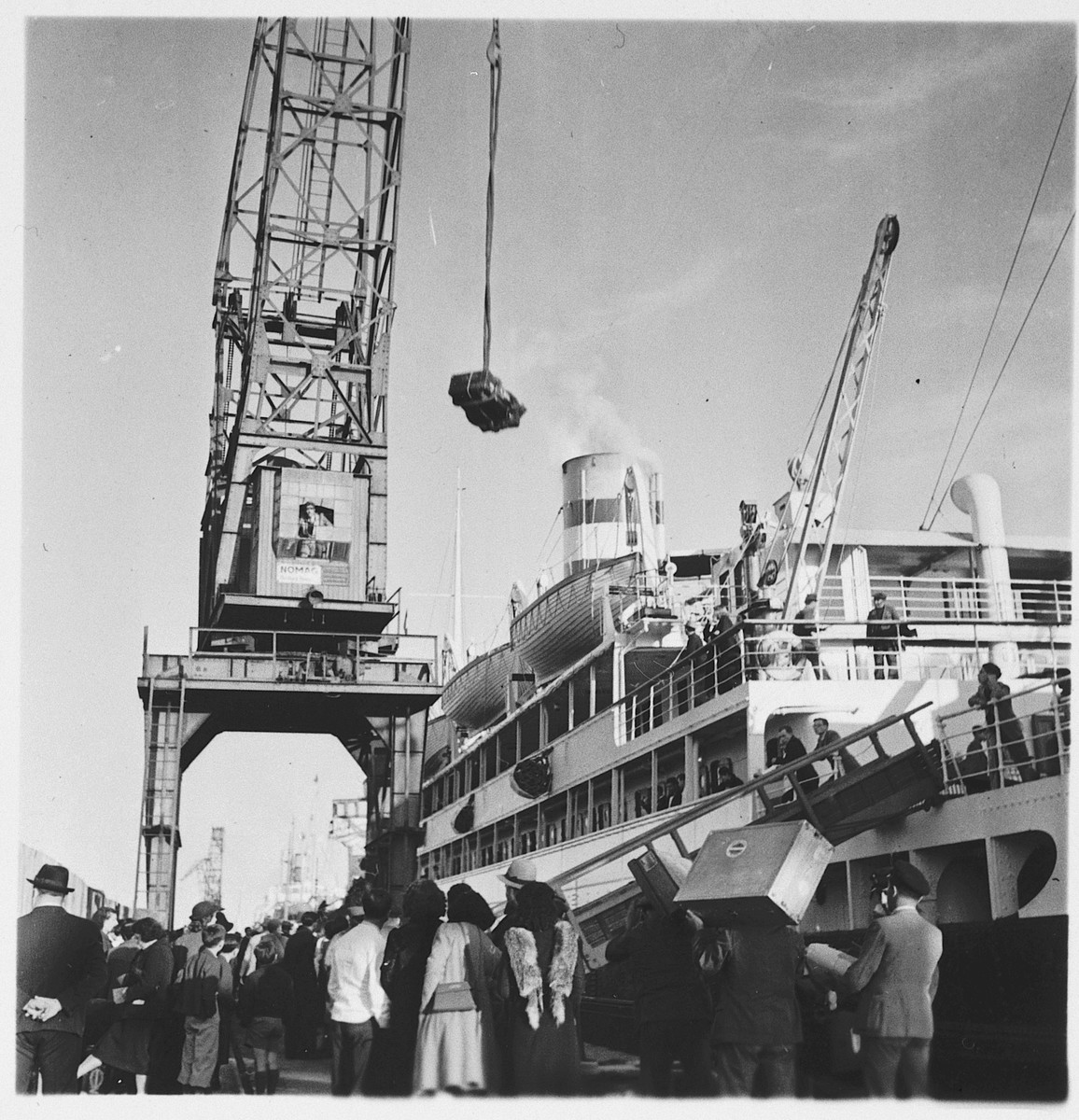 Jewish refugees watch as a crane is used to load their luggage onto the SS Serpa Pinto in the port of Lisbon.