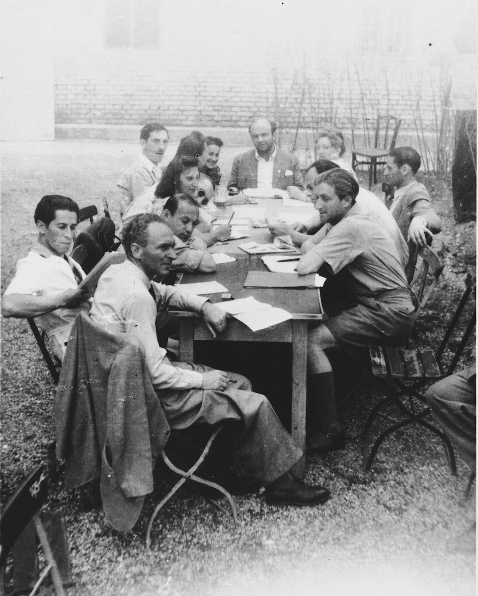 Members of the MIT (Munich Jewish Theater) theatrical group gather for a meeting in the Landsberg DP camp.  Pictured seated from left to right are Messinger, Weissman, Segel, Rosen, Halperin, Nathan, Litwine, Citron, Bardini, Karpinowitch, Rogin, Guttark, and Berman.