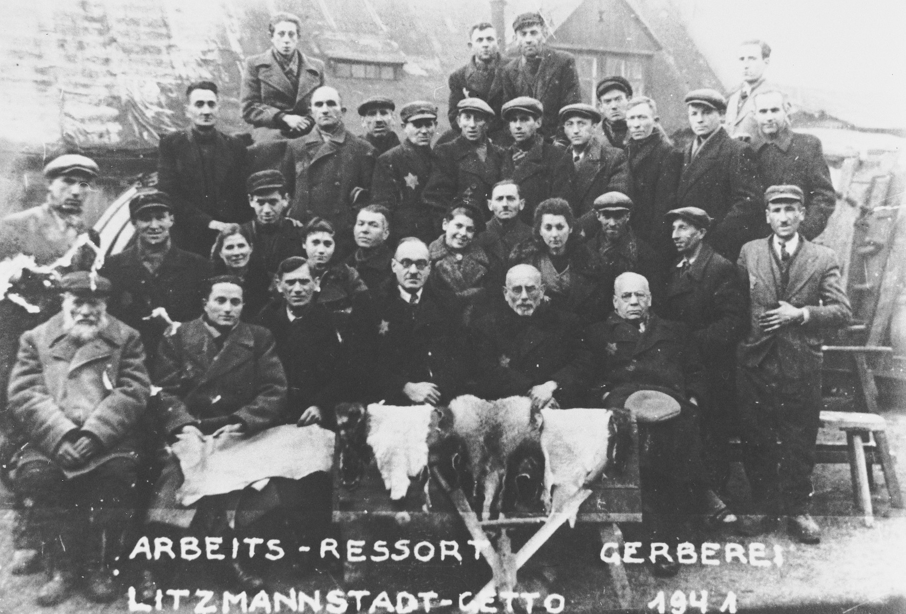 "Group portrait of the leather factory workers in the Lodz ghetto.  Shmuel Topilsky (grandfather of the donor) is pictured in the front row, second from the right.  Also pictured are Jacob Noech Galas (standing on far right in the second row from the front), Menachim Yehuda ""Moniek"" Galas (seated in the front row, second from left) and [perhaps the man seated to Menachim's right is Abram Michal Galas.]"