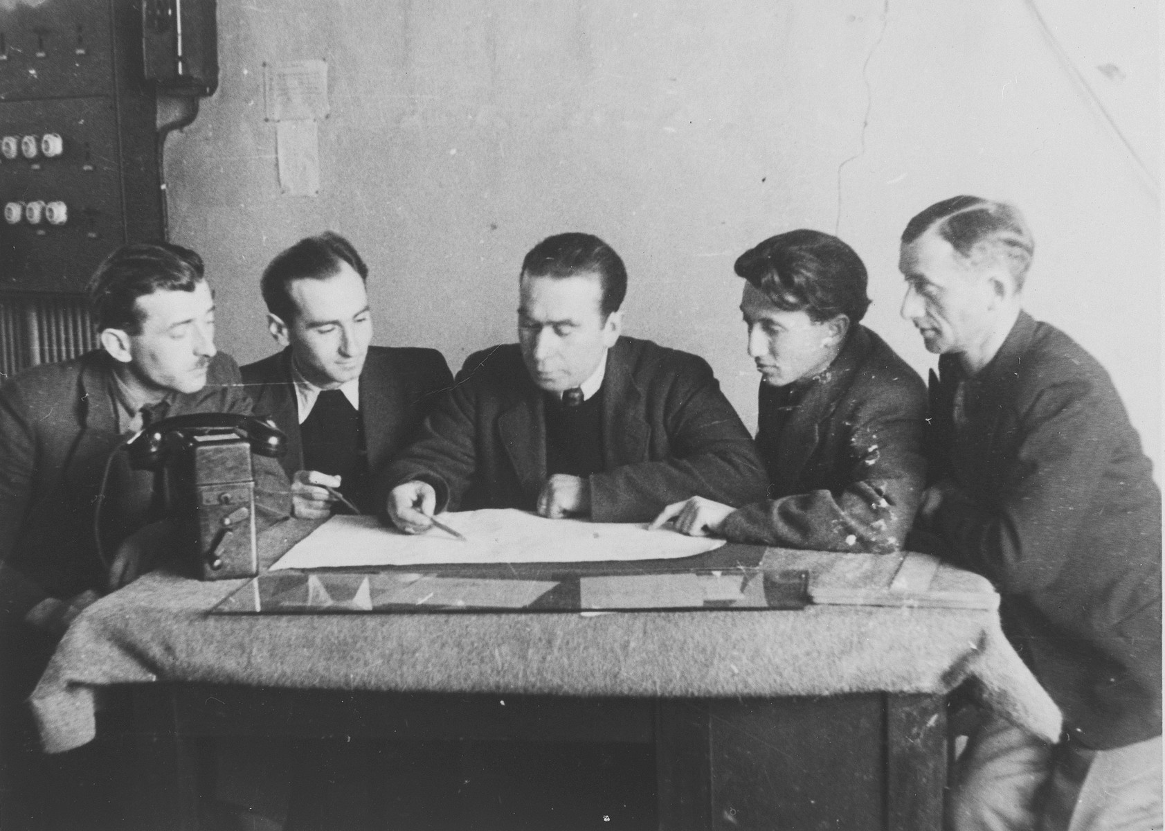 Edward Cittrons, director of ORT in Neu-Ulm, and four other men examine some plans on a table in his office.