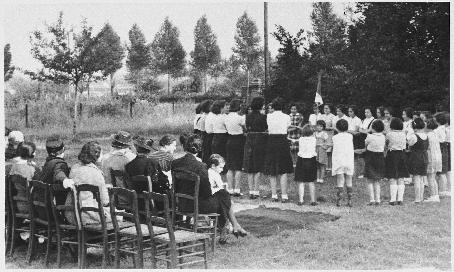 Supporters of the Zuen children's home watch the girls perform a flag-raising ceremony.  Among those seated is the director of the home, Mrs. Elka Frank.  Standing near the flag in the plaid dress is Else Rosenblatt (now Stern).