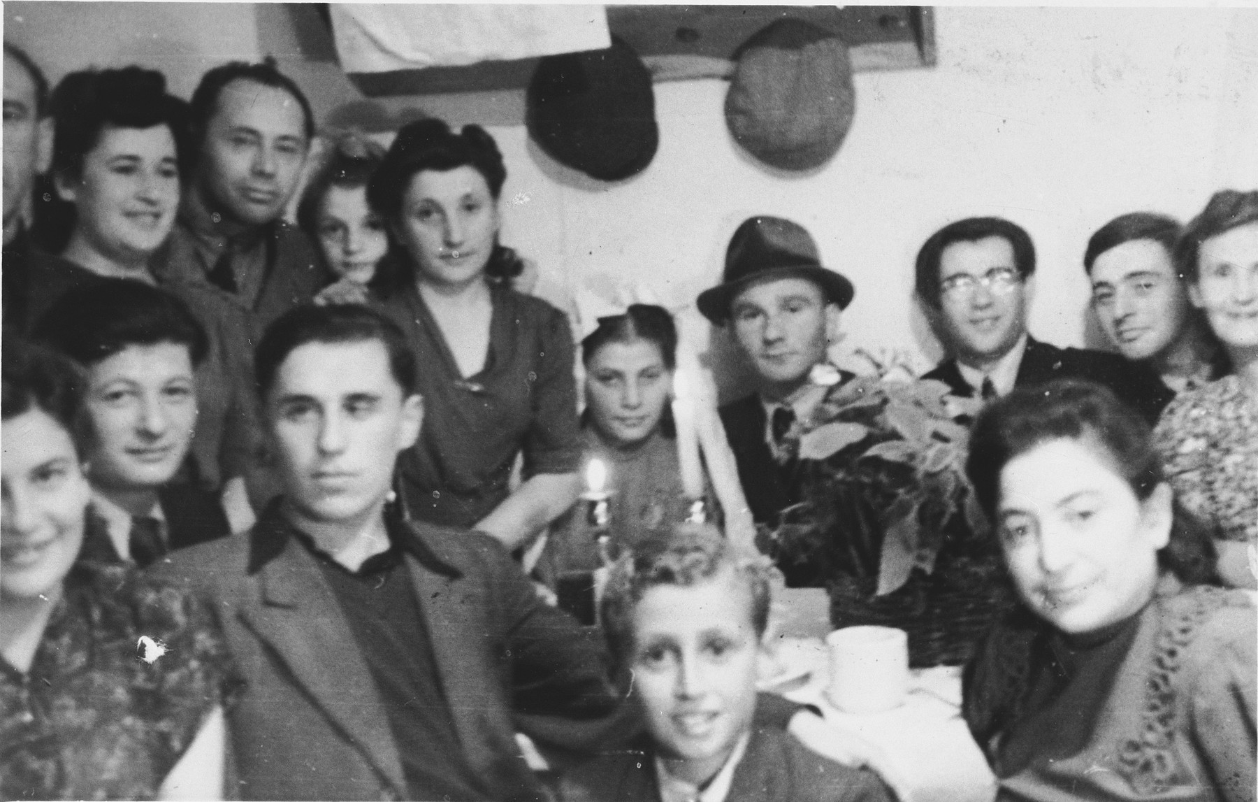 """A wedding party gathers around a table with two candles in the Schlachtensee displaced persons camp.  The inscription on the back reads, """"Ilub Piemiazek/I Liberman."""""""
