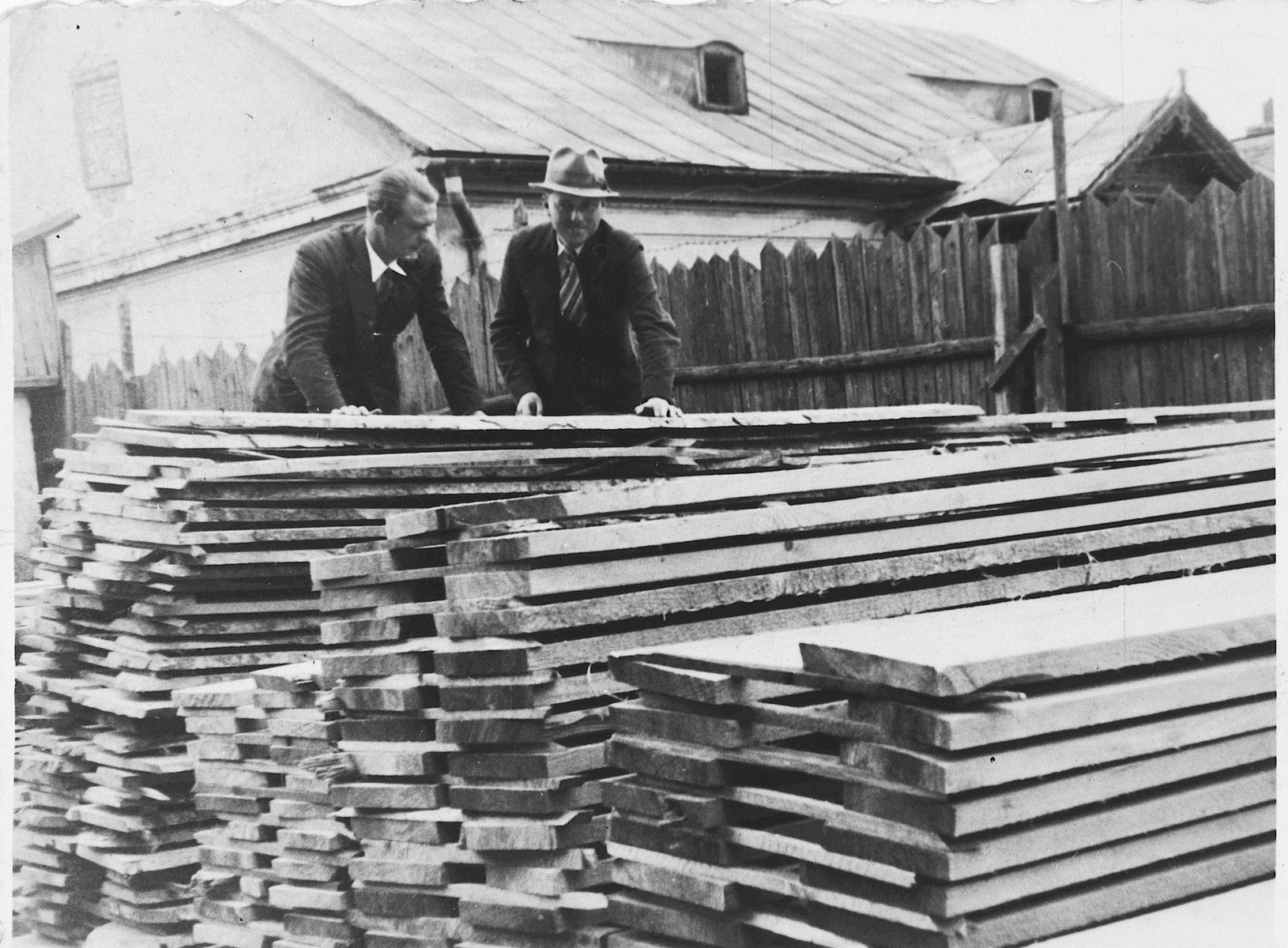 A Jewish lumber merchant talks to a customer in the family lumberyard in Rzeszow, Poland.   Among those pictured is Aron Jam (right).