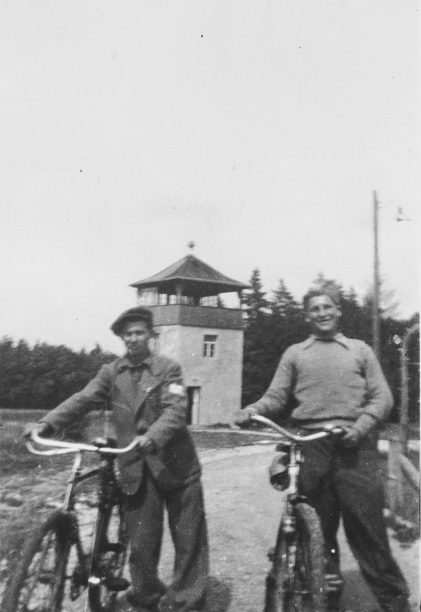 Two Jewish teenagers ride bicycles through Buchenwald prior to their leaving the camp for Switzerland.  Pictured on the left is Abraham Grajz.