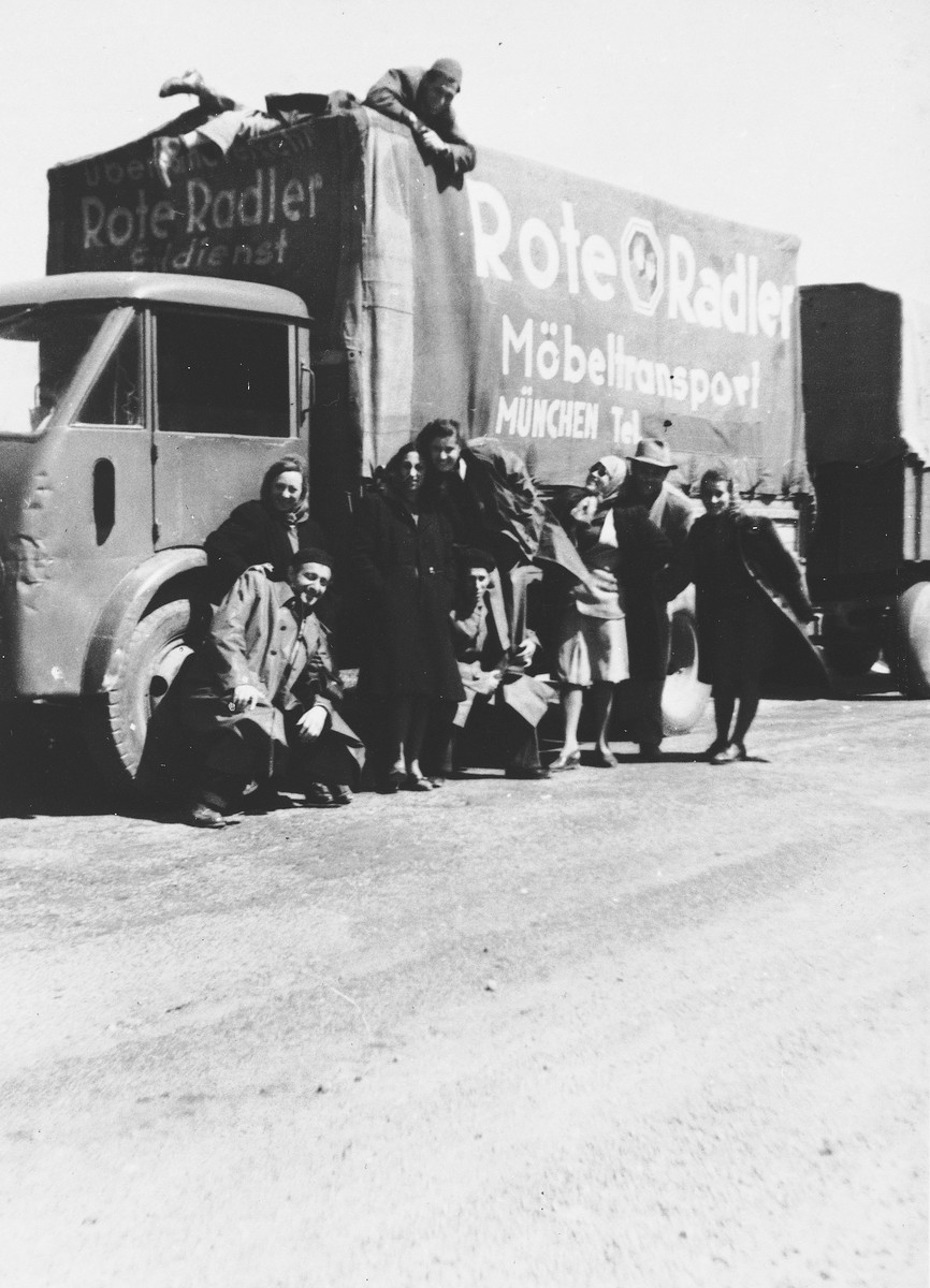 Members of the Landsberg MIT (Munich Jewish Theater) theatrical group stand next to a moving van.  Pictured from left to right.  First row: Weissman, Citrinah and Siegel.  Middle row: Woltevchik, Halperin. Betti Siegel, Shaar, Bardini, Litvina, Guttmark, Karpinowitch, and Rechi Berman.  Back row: Rosenberg, Nathan.