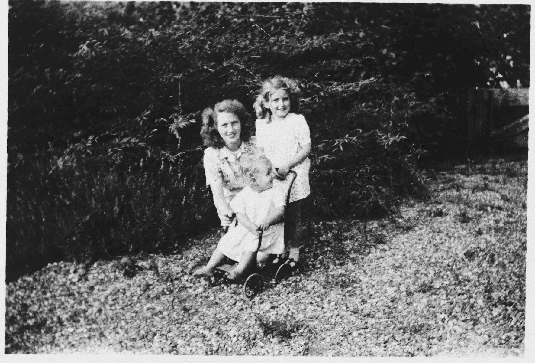 Polly Hertz plays with her rescuers' children, Liberta (b. 1945) and Marjolein (b. 1941), on a return visit to the family in 1946.